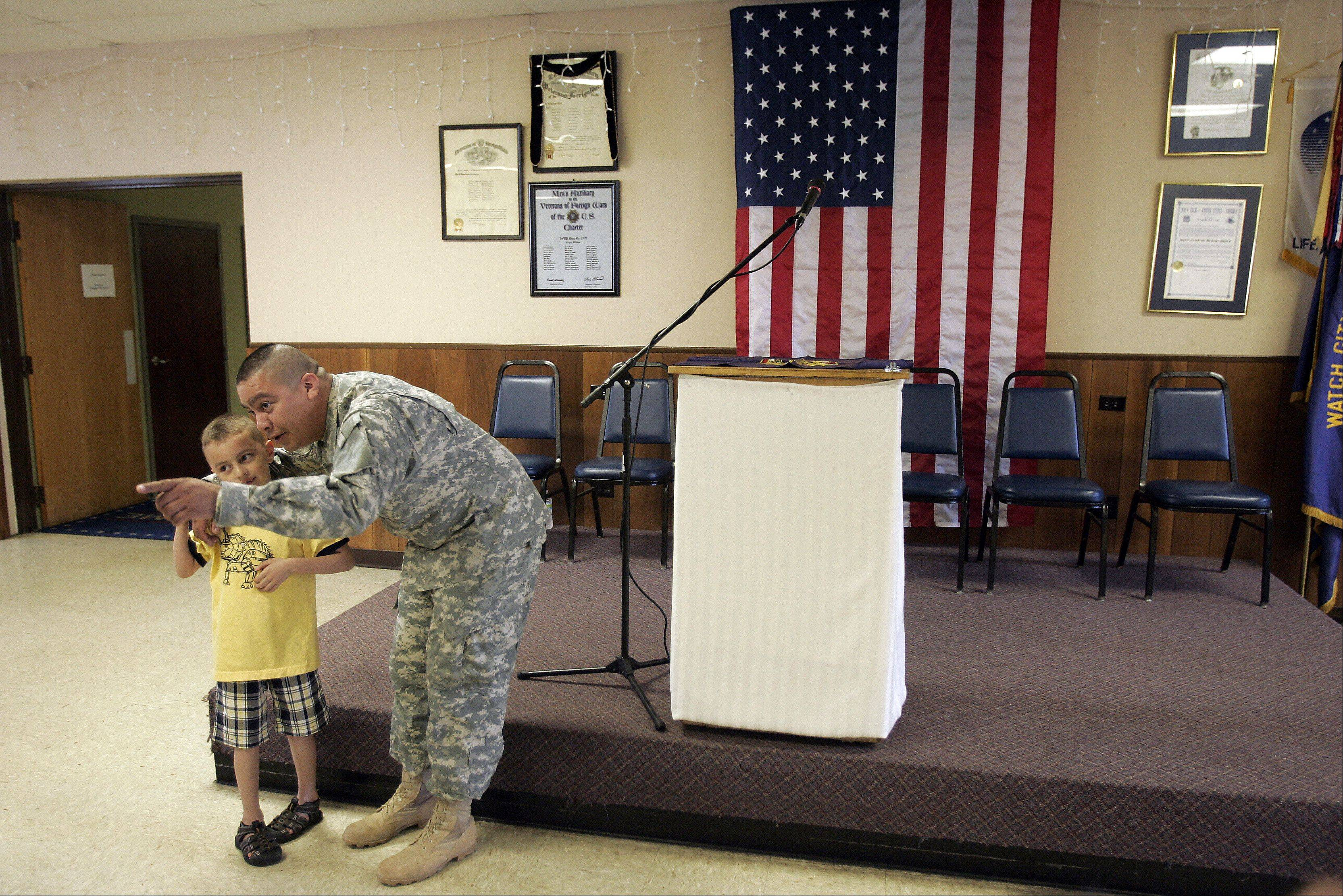Retired U.S. Army Sgt. Michael Griffin shares a moment with his son Michael Griffin II, 6, after receiving the Army Commendation Medal of Valor Thursday during a celebration at VFW Post 1307 in Elgin.