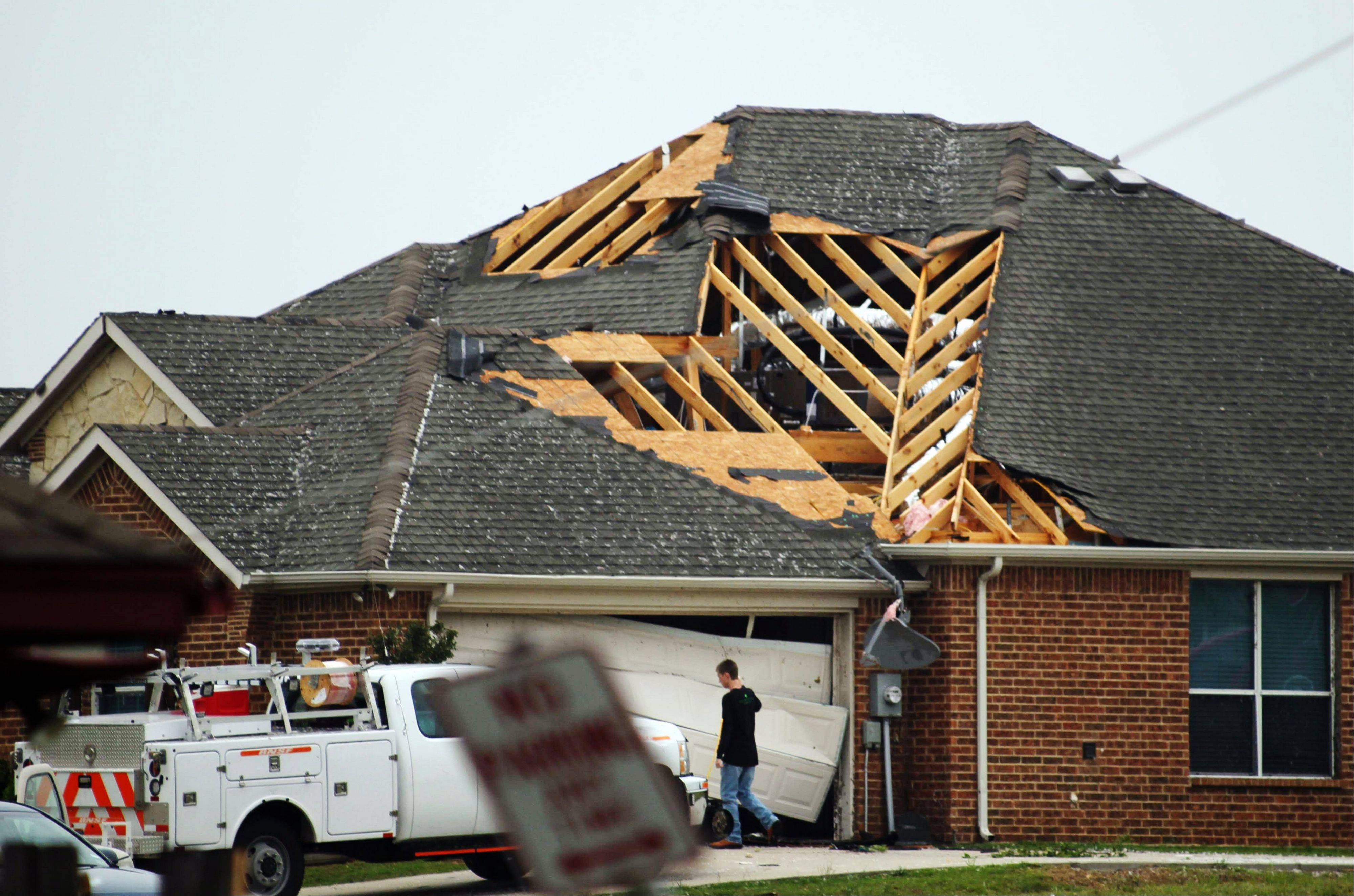 A man walks in front of a home damaged by Wednesday's tornado in Cleburne, Texas on Thursday, May 16, 2013. Ten tornadoes touched down in several small communities in Texas overnight, leaving at least six people dead, dozens injured and hundreds homeless. Emergency responders were still searching for missing people Thursday afternoon. (