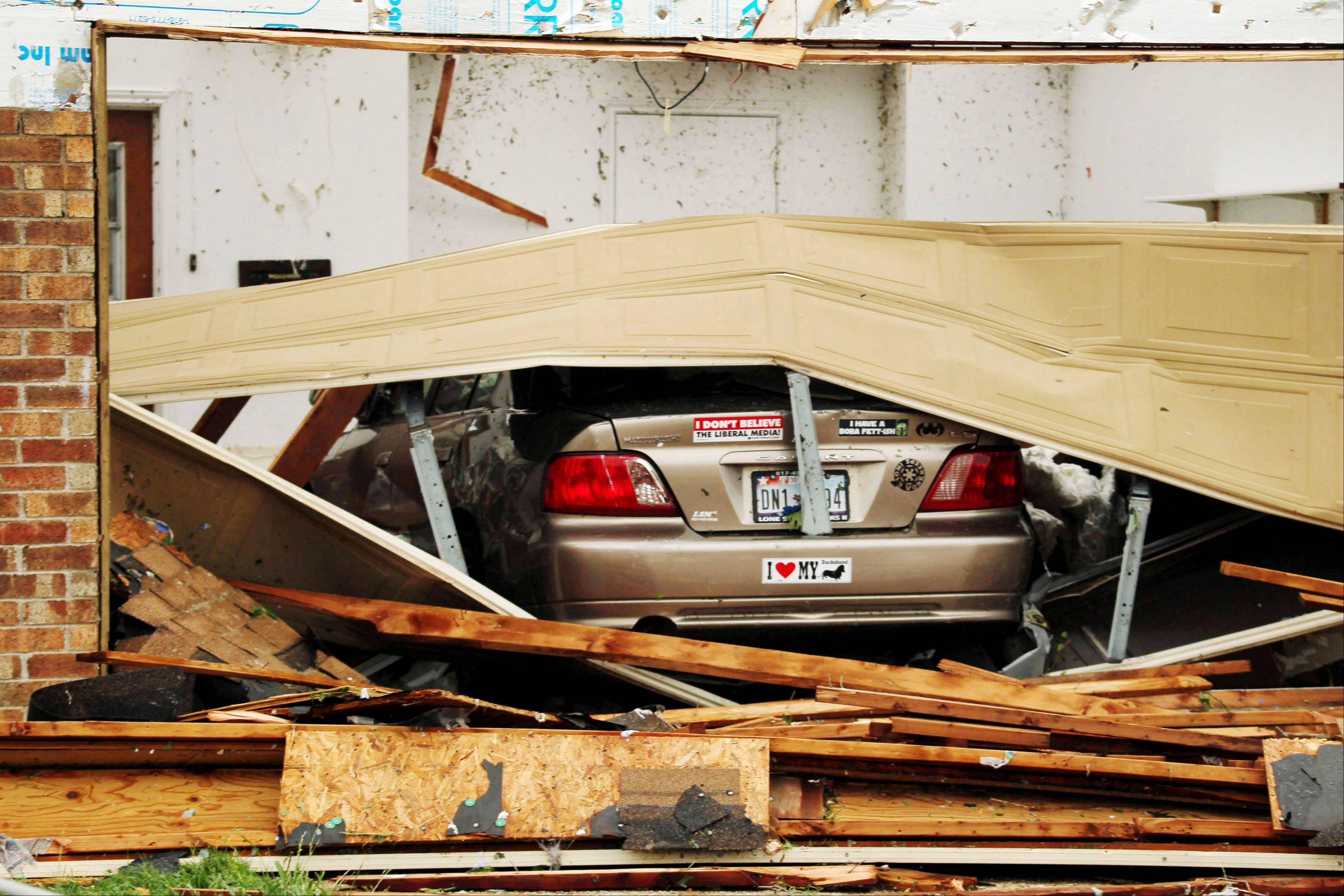 A car is seen in a damaged home after Wednesday's tornado in Cleburne, Texas on Thursday, May 16, 2013. Ten tornadoes touched down in several small communities in Texas overnight, leaving at least six people dead, dozens injured and hundreds homeless. Emergency responders were still searching for missing people Thursday afternoon.