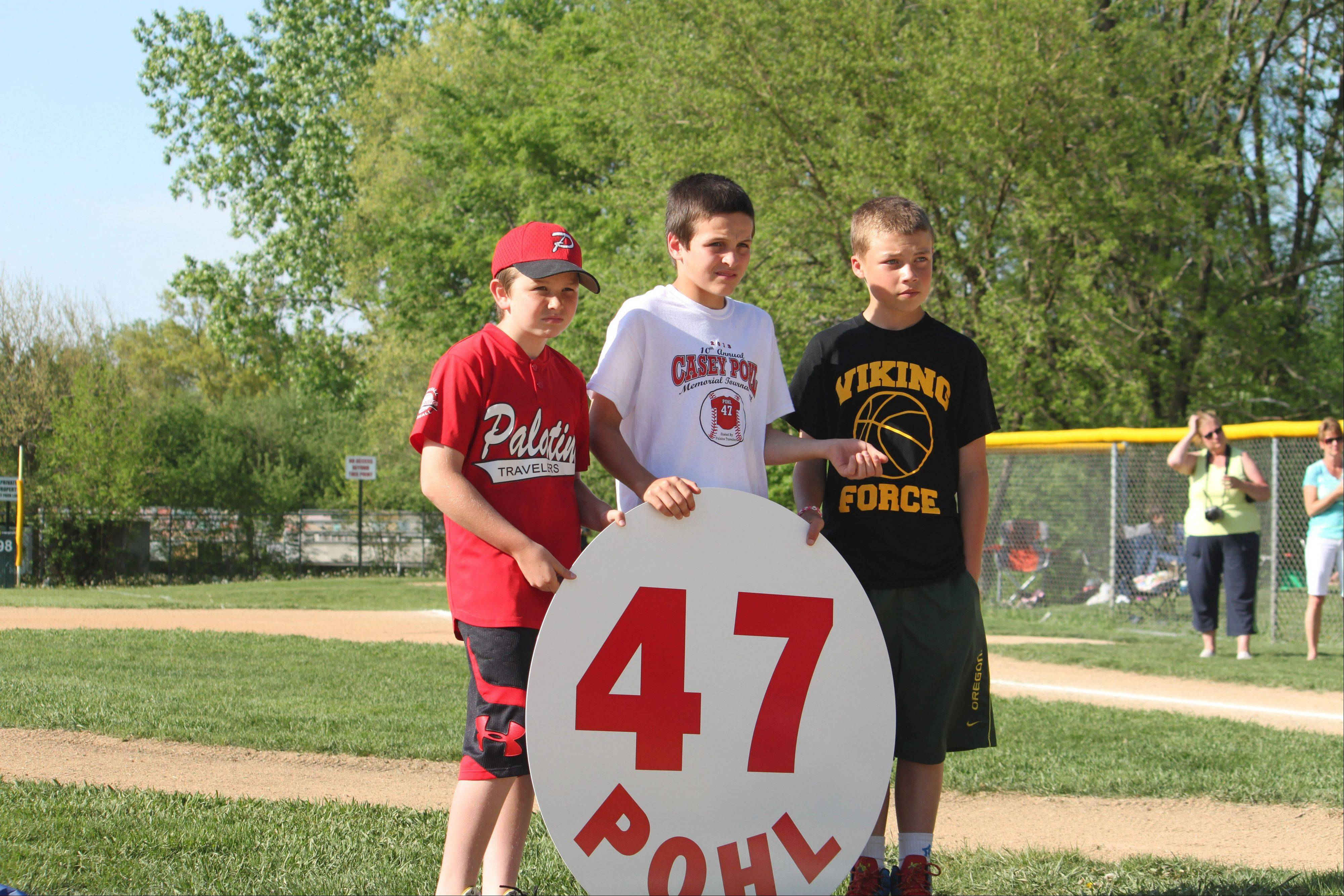 Ben Kurka, Austin Higgins and Will Ferry hold a placard bearing Casey Pohl's name and number that will be affixed to the outfield wall at Fuller Field in Palatine. Pohl died in 2003 from cancer.