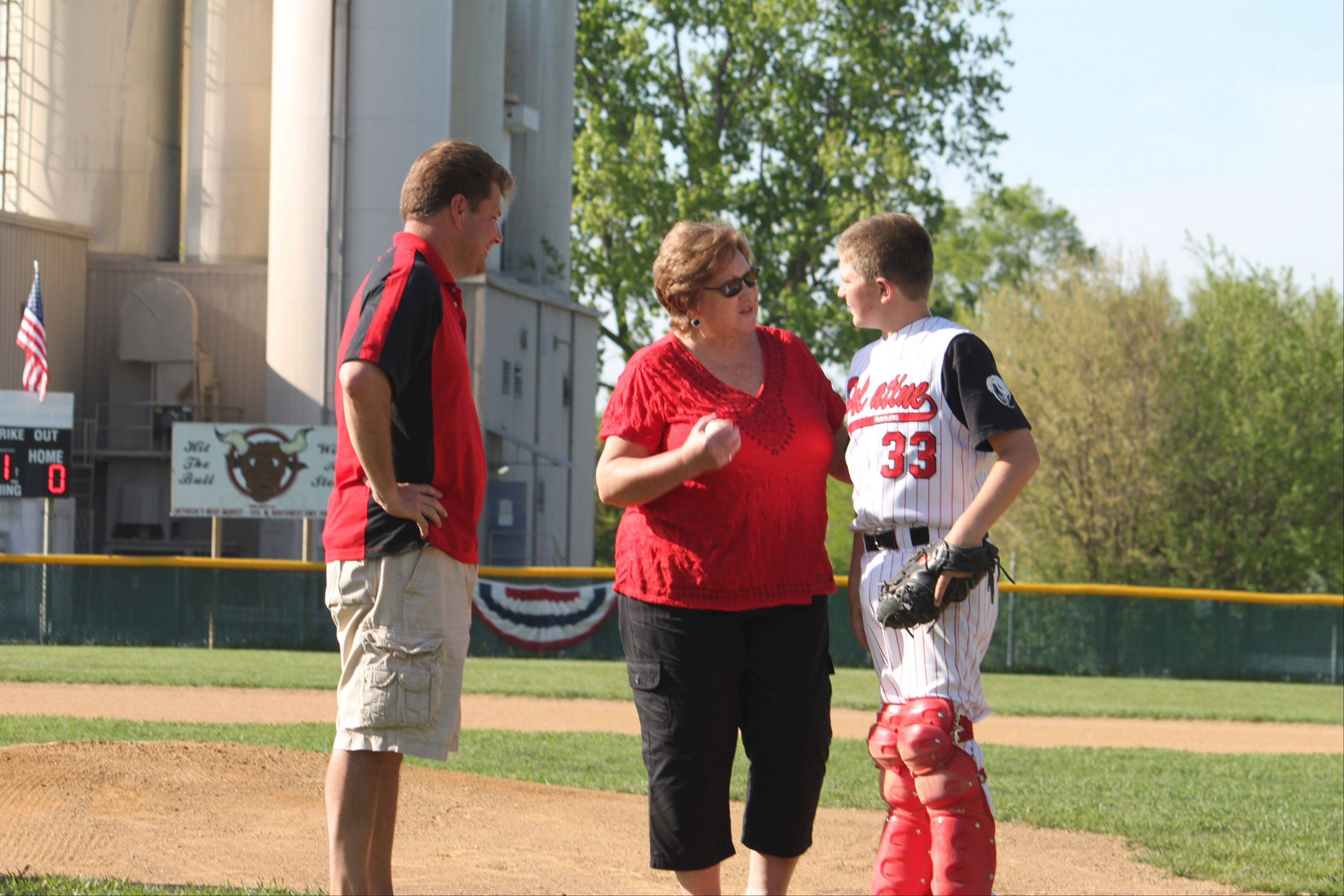 Debbie Pohl talks with catcher Will Josten and tournament director Chris Bechtold after throwing out the first pitch Thursday at the Casey Pohl Memorial Tournament.