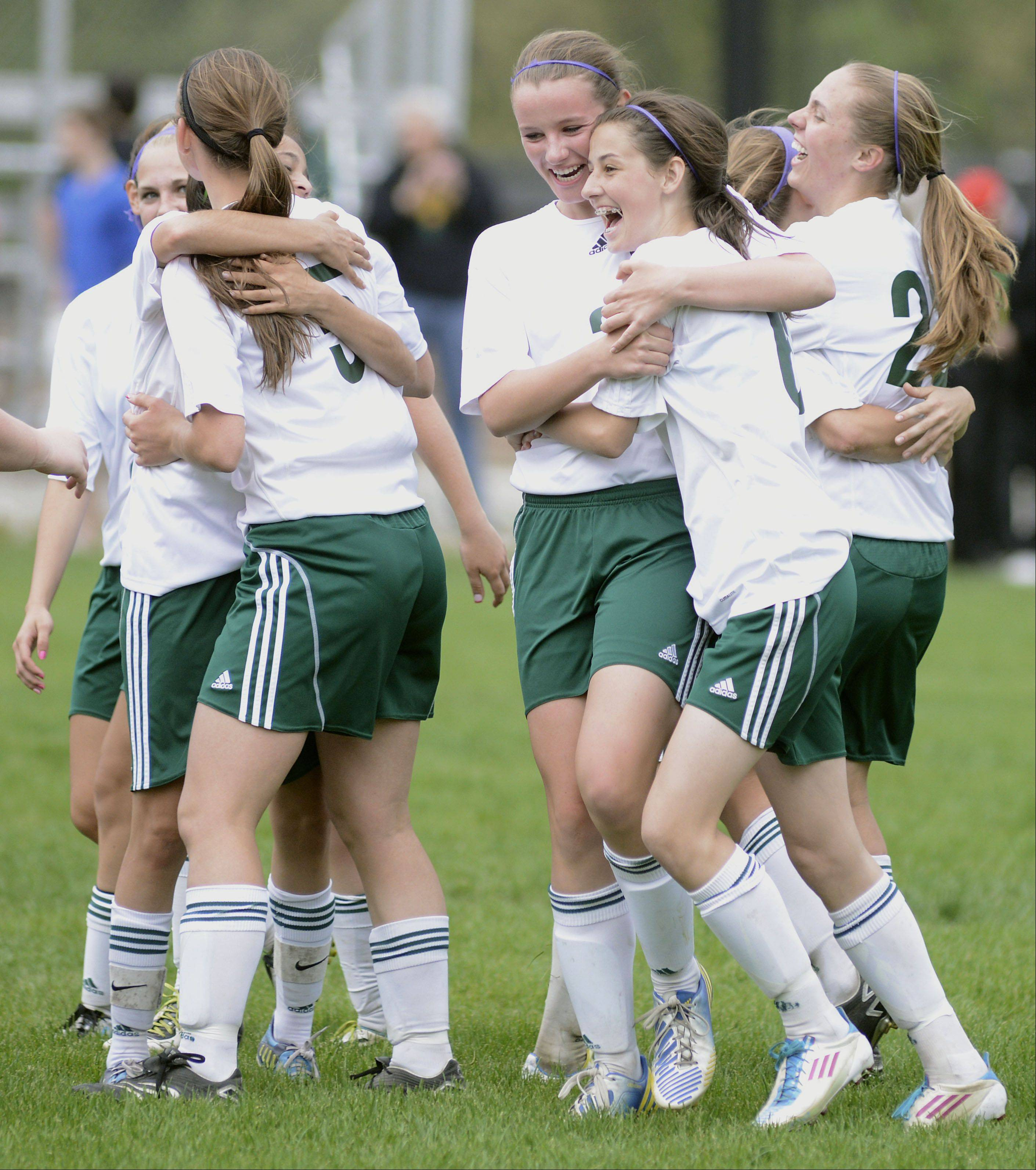 St. Edward's Kathleen Duffy, left, and Chelsea Gnan celebrate with their Green Wave teammates after winning the Class 1A Westminster Christian sectional title on Friday.