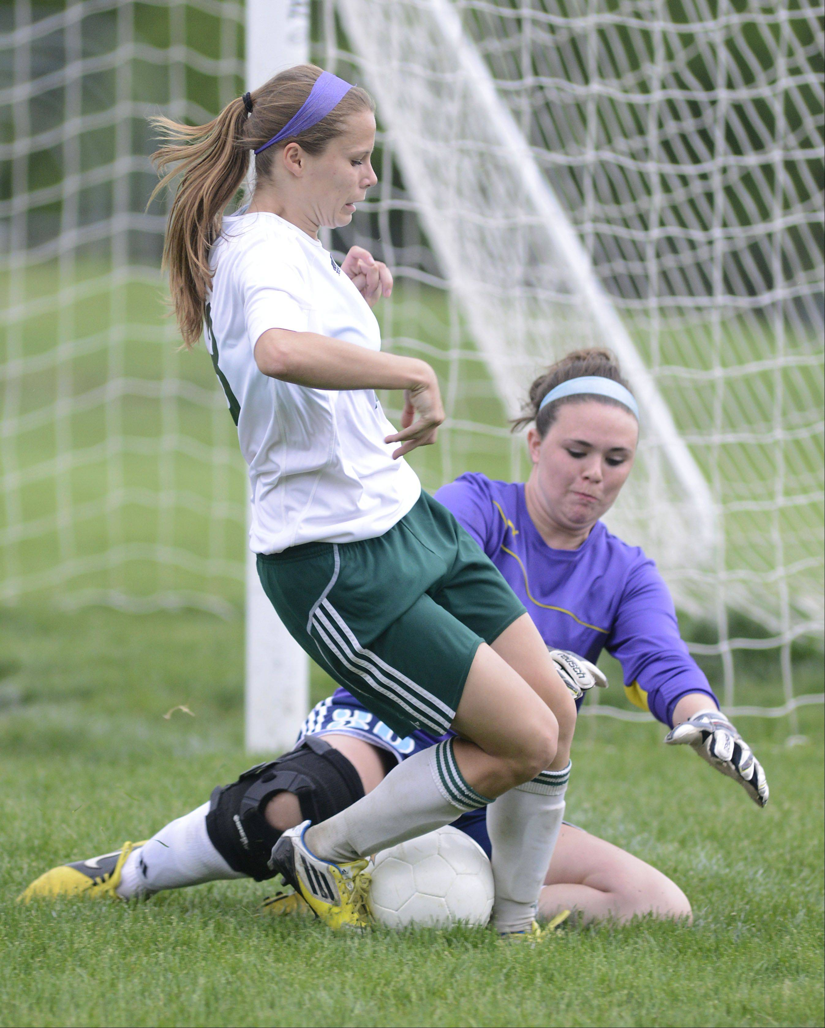 Willows Academy goalie Bethy Hunt attempts to capture the ball as St. Edward's Meagan Kearney tries to redirect it back toward the front of the net in the first half of the Class 1A girls soccer sectional title game on Friday, May 17.