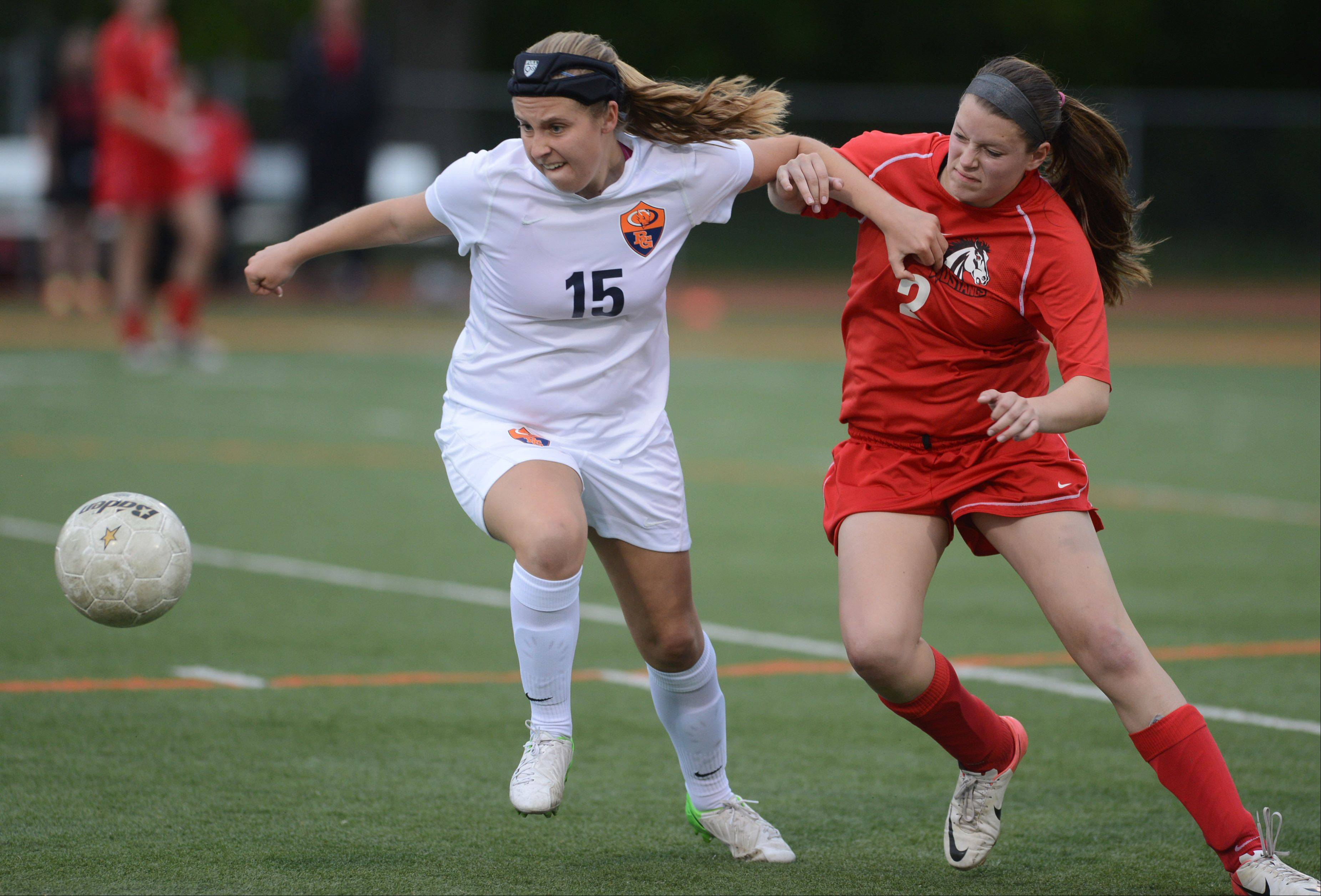 Buffalo Grove's Kelly VandeMerkt (15) and Mundelein's Shannon Carroll chase down a loose ball during Friday's Class 3A girls soccer regional final at Libertyville.