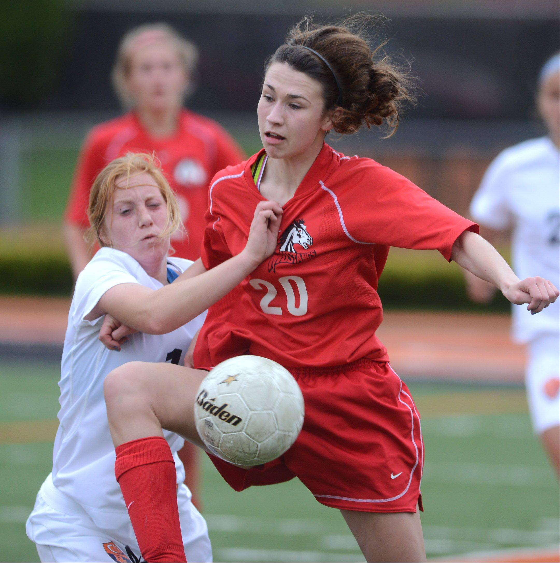 Mundelein's Jessica Schultz (20) controls the ball under pressure from Buffalo Grove's Kelli Zickert during Friday's Class 3A girls soccer regional final at Libertyville.