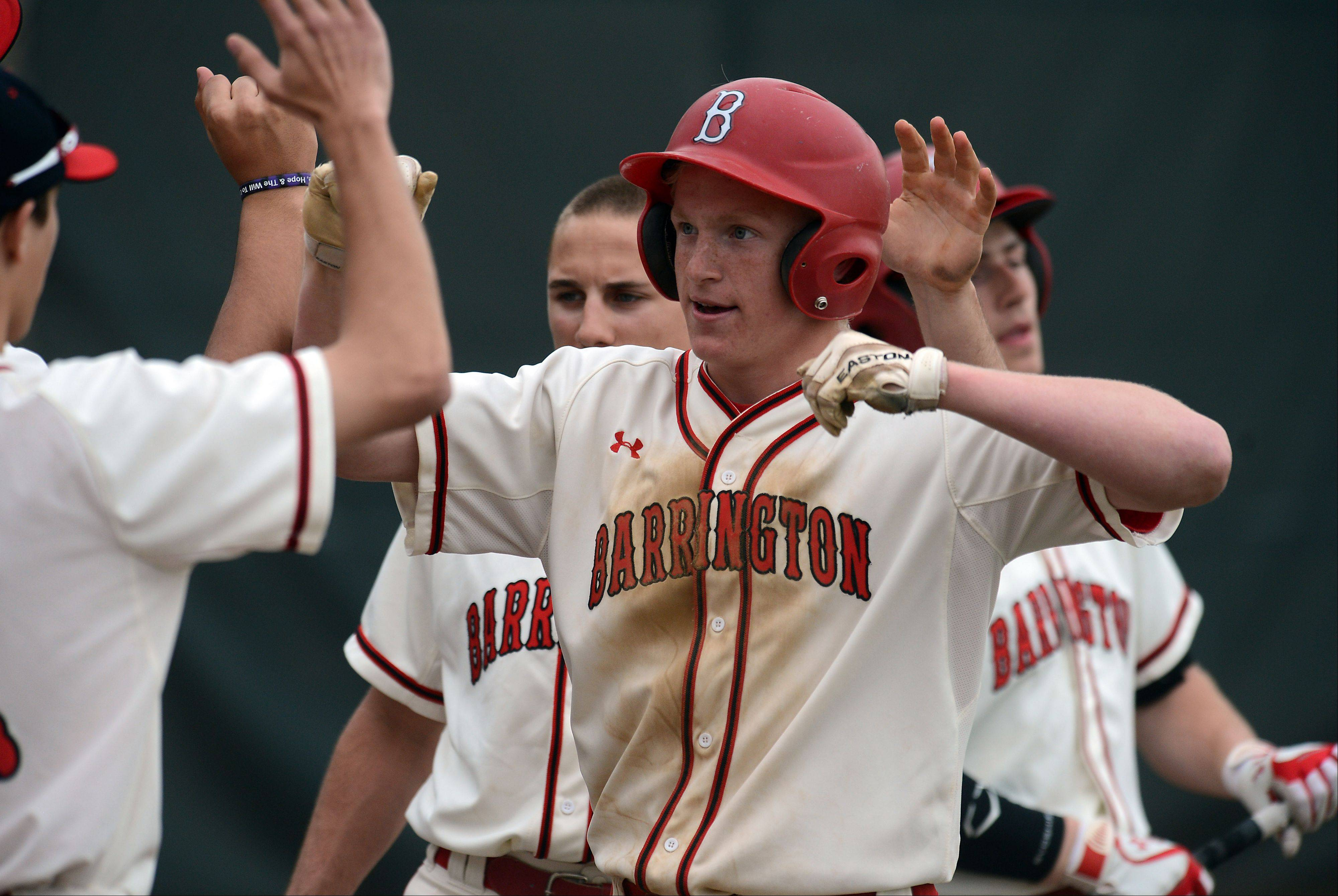 Barrington's Mitch Pfeiffer celebrates with his teammates after scoring the first run of Friday's MSL championship game against host Rolling Meadows.