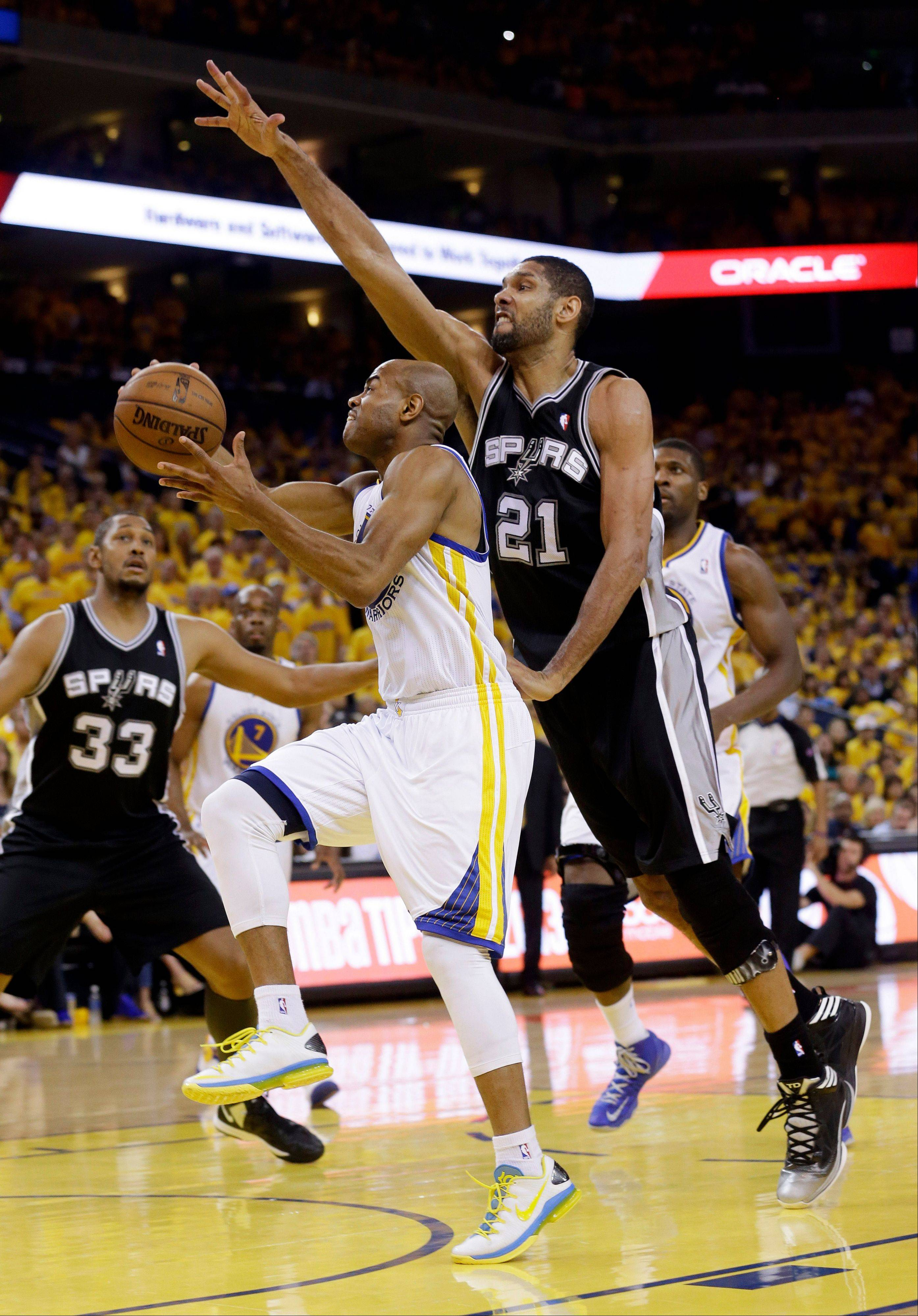 Golden State Warriors point guard Jarrett Jack (2) drives to the basket as San Antonio Spurs forward Tim Duncan (21) attempts to block in the second half of Game 6 of a Western Conference semifinal NBA basketball playoff series in Oakland, Calif., Thursday, May 16, 2013.