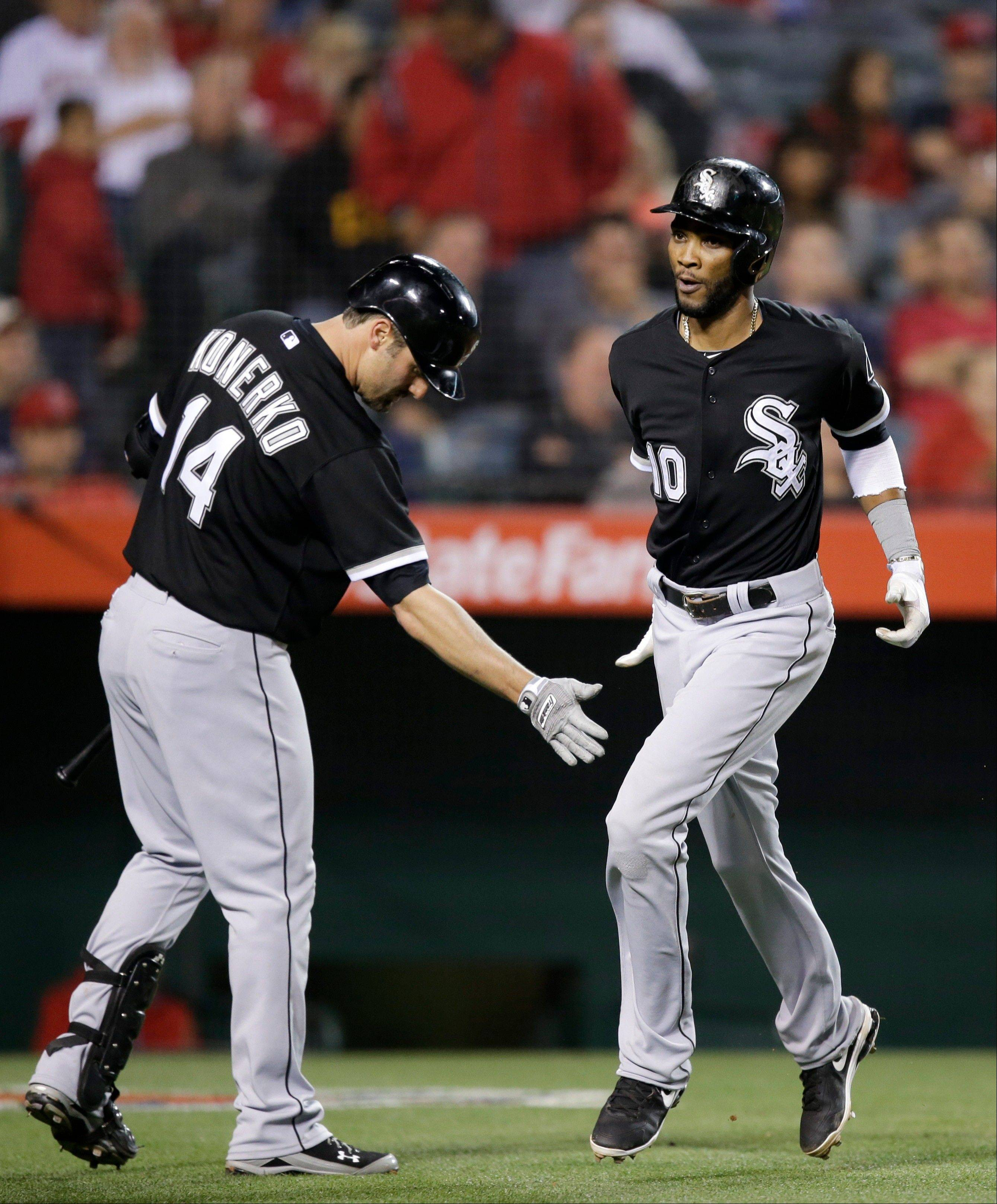 Chicago White Sox's Alexei Ramirez, right, is greeted by Paul Konerko after he scored on a single by Adam Dunn during the eighth inning of a baseball game against the Los Angeles Angels in Anaheim, Calif., Thursday, May 16, 2013.
