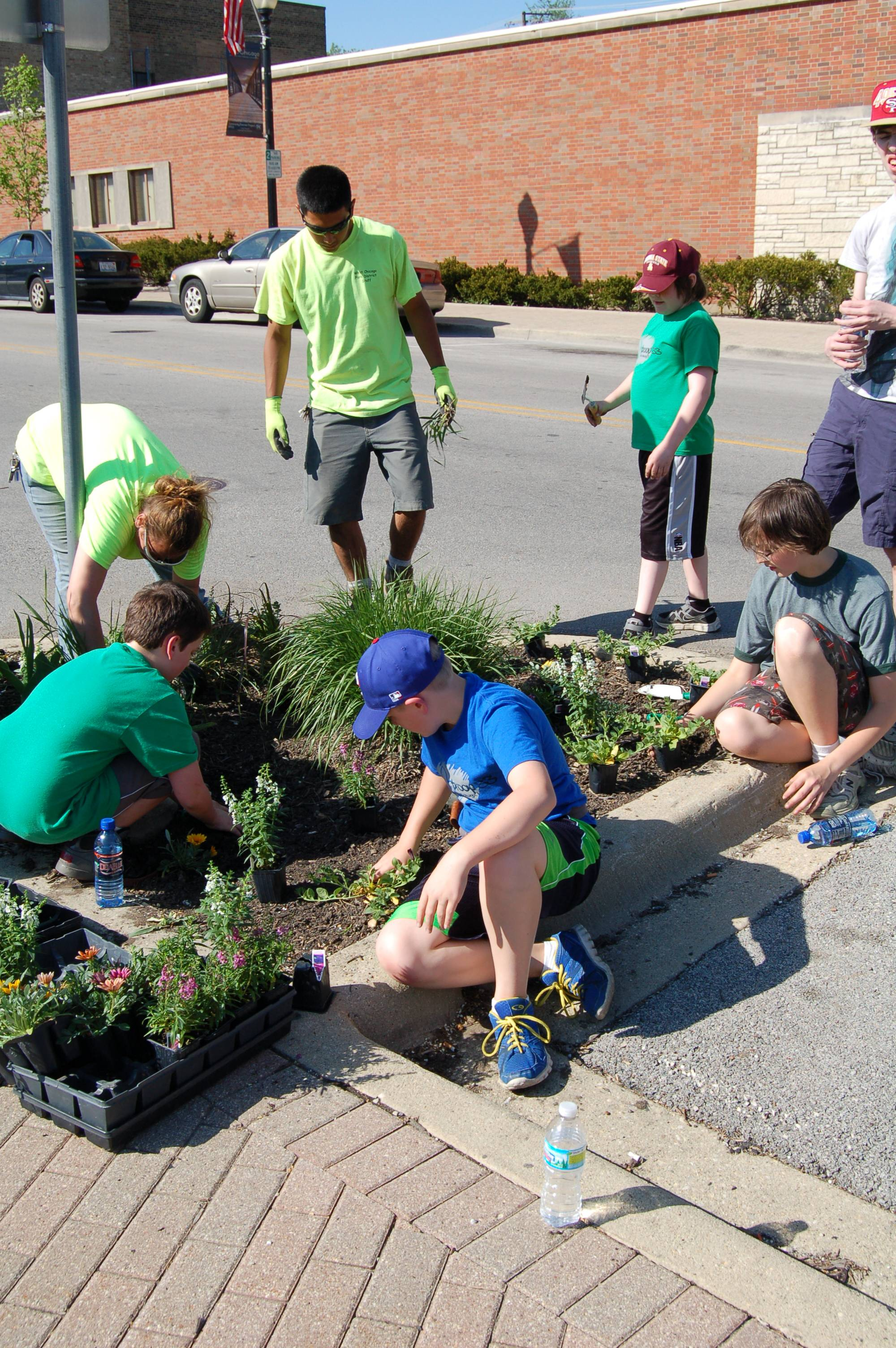 West Chicago Park District staff work along side Boy Scouts and Troop Leaders from Troop #33 on downtown garden beds.