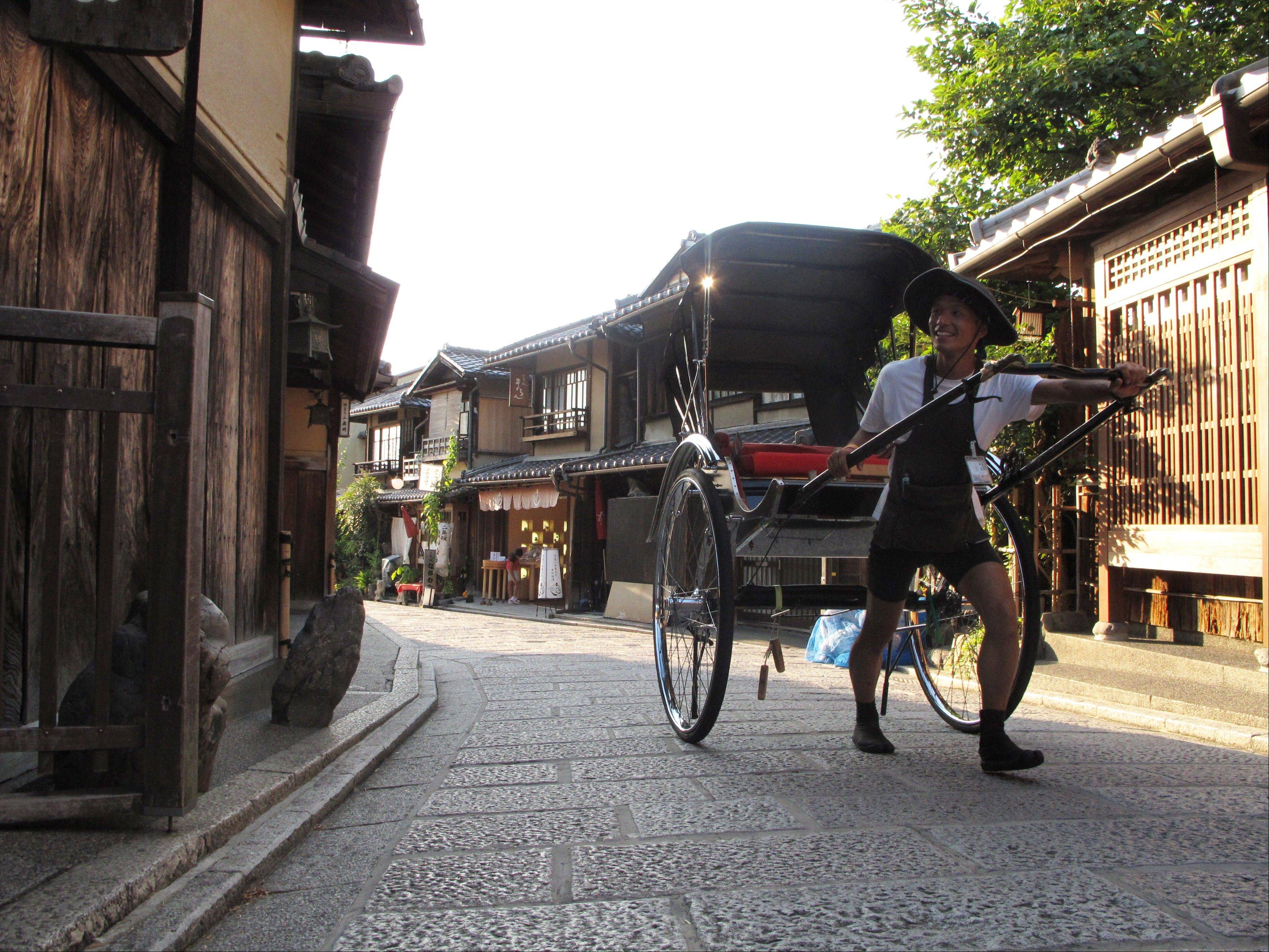 A man pulls a rickshaw-for-hire down a narrow street in Kyoto, Japan, near the city's Kiyomizu Temple. The temple and surrounding neighborhood are a great place to explore for families with children.