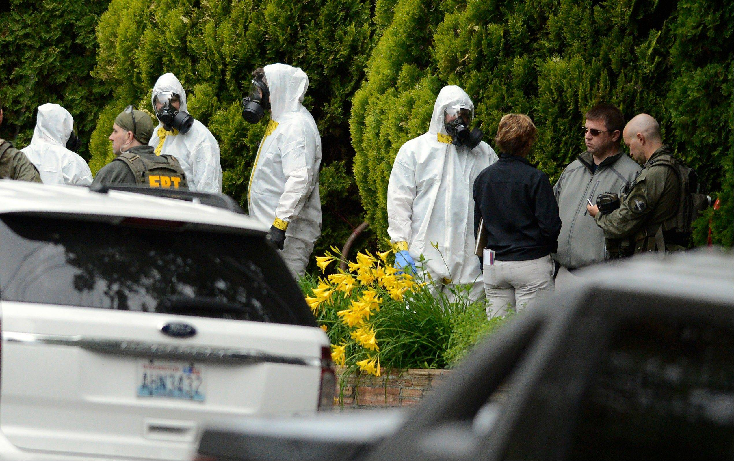 During the execution of a search warrant, members of the Joint Federal Haz-Mat Team, FBI, and local law enforcement gather Saturday in front of the Osmun Apartments near the intersection of First Avenue and Oak Street in Spokane, Wash.