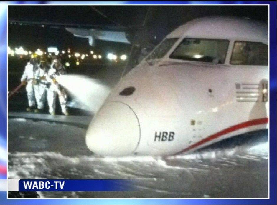 Emergency personnel spray foam on the fuselage of a US Airways Express commuter plane after it made a belly landing Saturday morning at Newark Liberty International Airport.