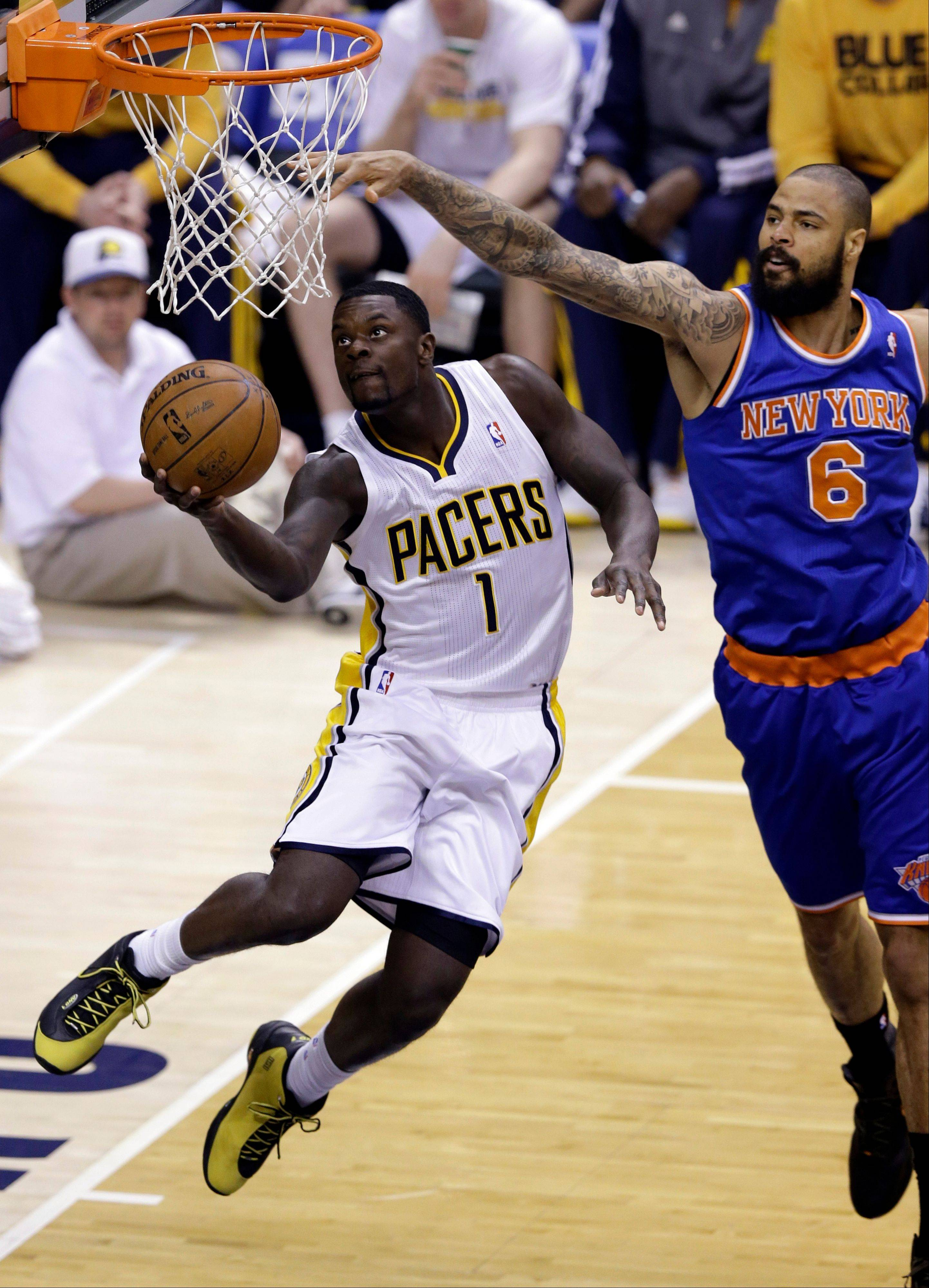 Indiana Pacers guard Lance Stephenson (1) gets a basket under New York Knicks center Tyson Chandler Saturday night during Game 6 of the Eastern Conference semifinal NBA basketball playoff series in Indianapolis.