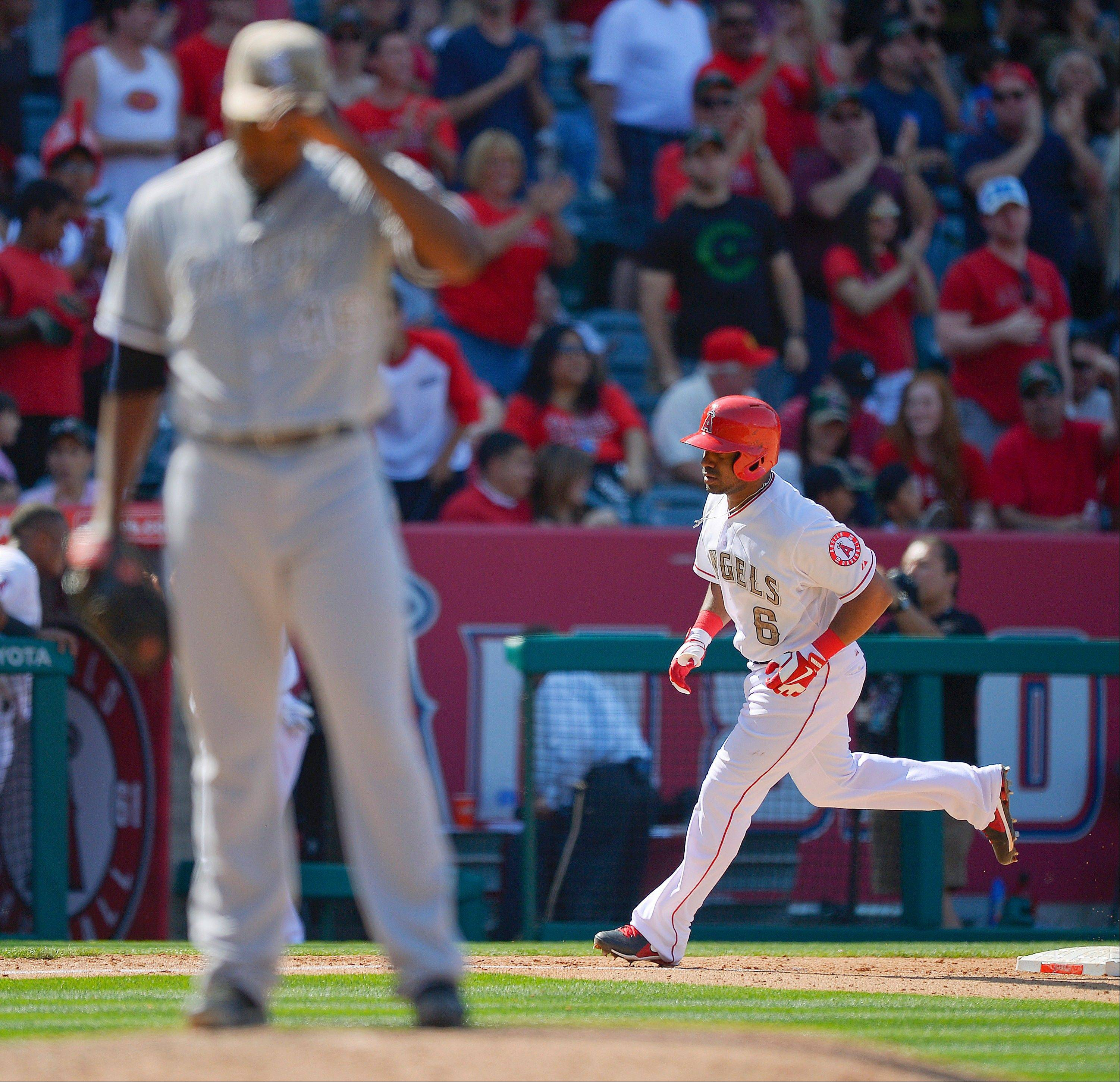 Los Angeles Angels' Alberto Callaspo (6) rounds the bases on a three-run home run off Chicago White Sox relief pitcher Donnie Veal, foreground, during the seventh inning of a baseball game, Saturday, May 18, 2013, in Anaheim, Calif. (AP Photo/Mark J. Terrill)