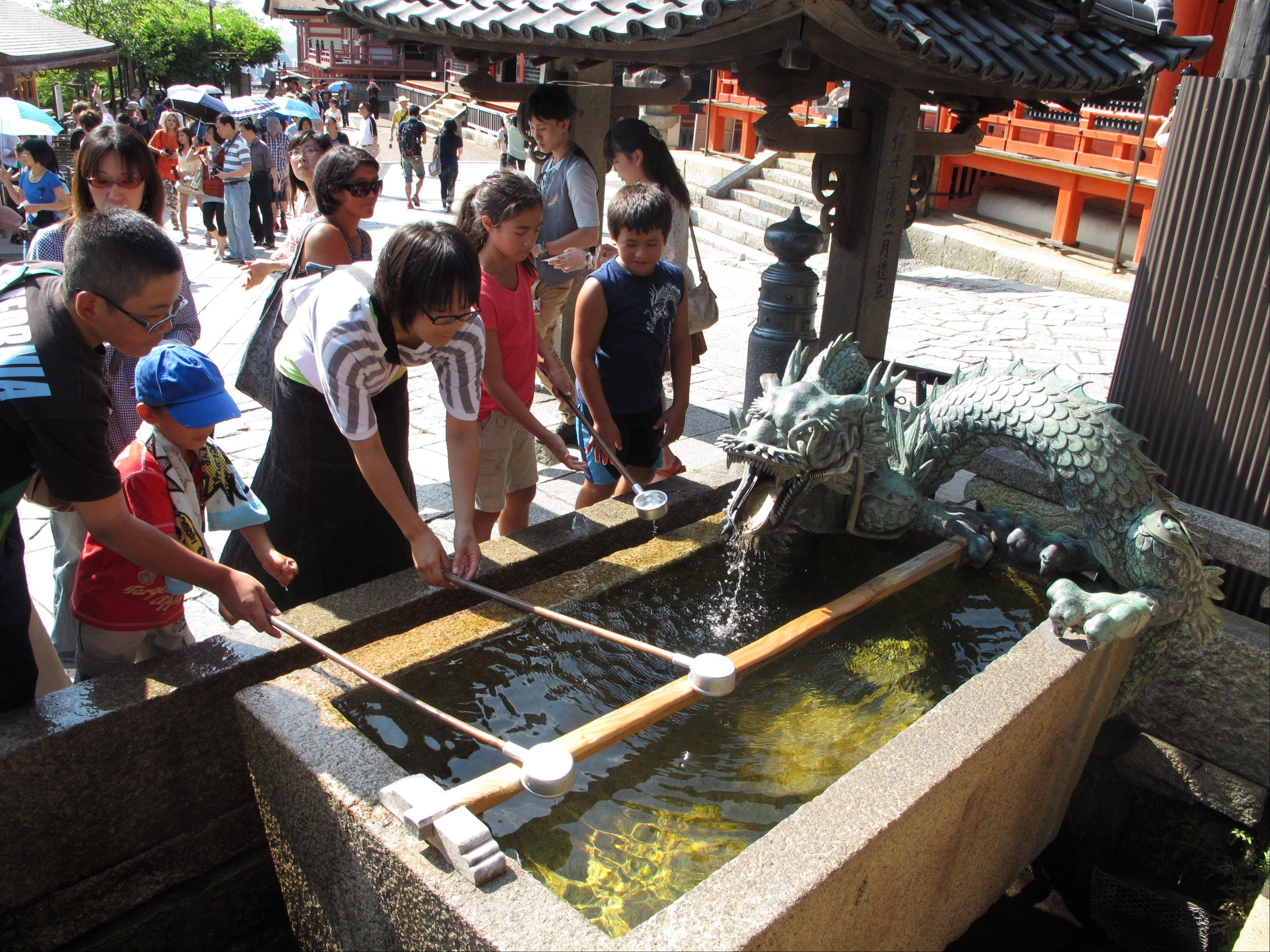 Visitors scoop water from a fountain near the entrance to Kiyomizu Temple in Kyoto.