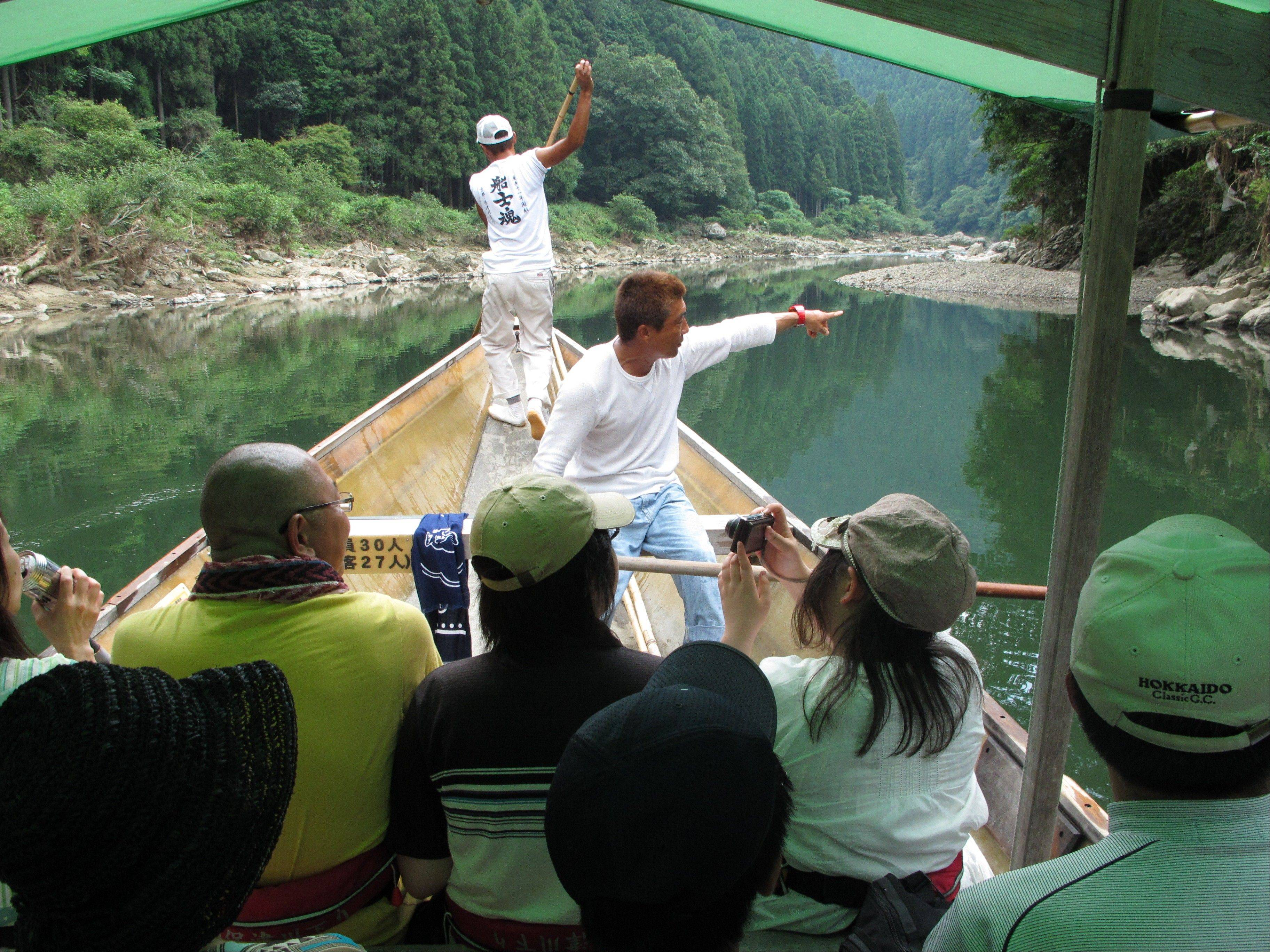 An oarsman pilots an excursion boat down the Hozu River, just outside Kyoto, as he points out sights to his passengers.