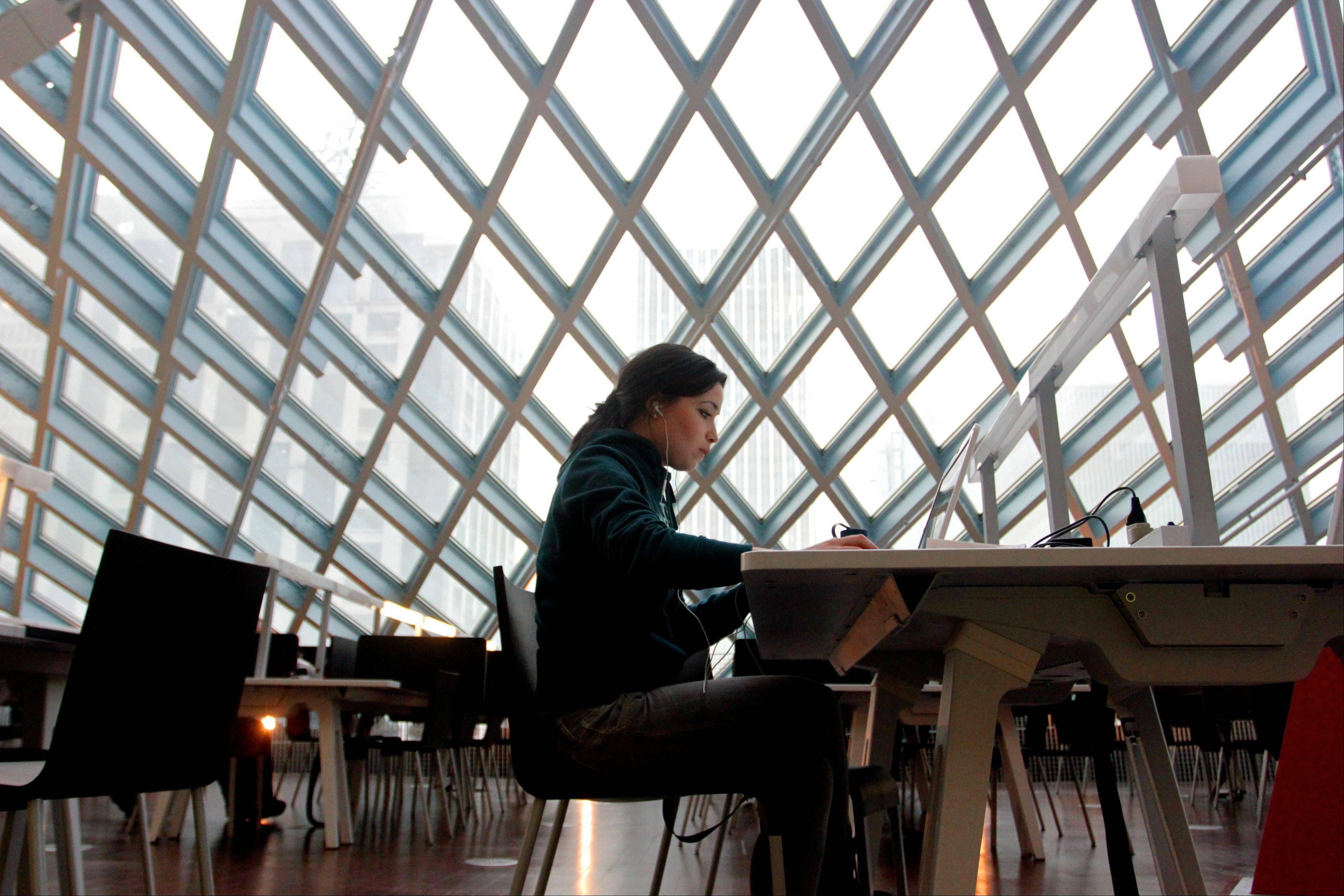A woman works on her laptop at the Seattle Central Library in downtown Seattle.
