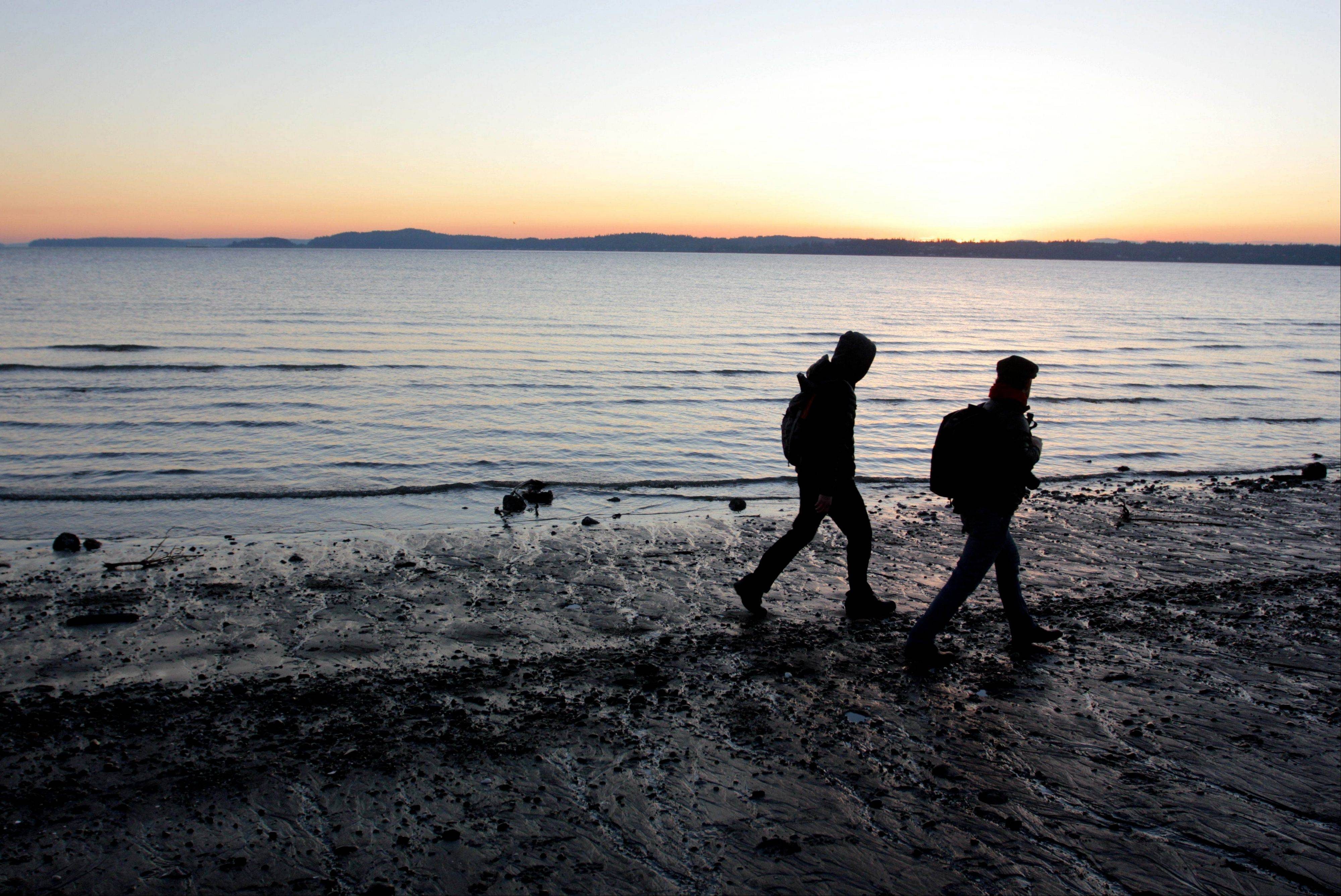 Two people walk the beach at Discovery Park in Seattle. At 534 acres, the park is the largest park in the city and features seaside bluffs, views of the Puget Sound, trails, a lighthouse and a beach.