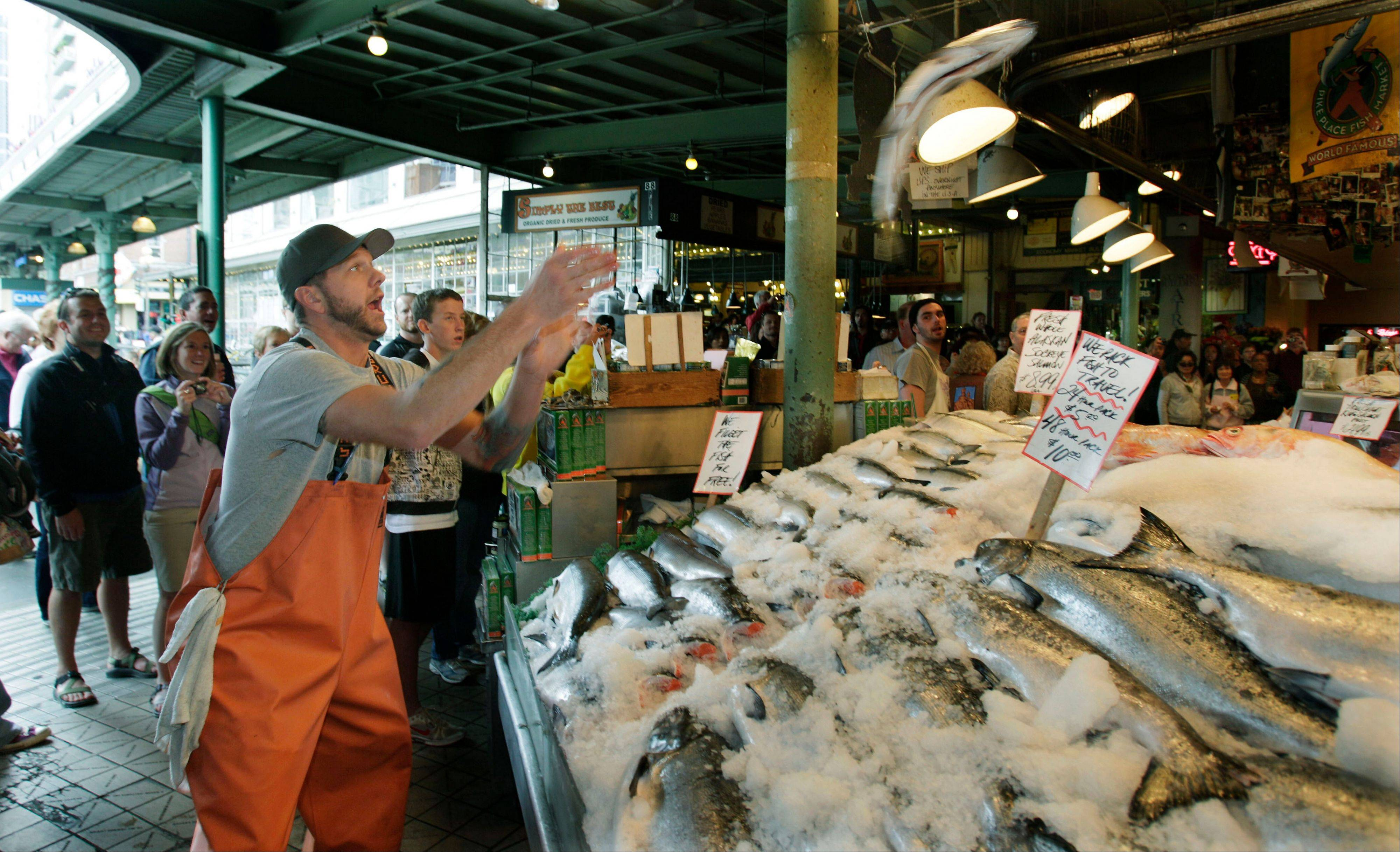 Justin Hall throws a salmon to a co-worker behind the counter at Pike Place Fish in Seattle.