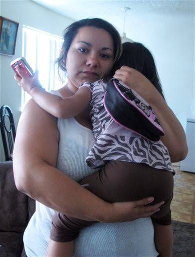 "Melissa Torrez, 27, holds her 4-year-old daughter in her apartment in Albuquerque, N.M., Friday, May 17, 2013. Torrez chased down a man for miles and ran into his car Wednesday, May 15, after he abducted her daughter. She told The Associated Press her ""mother's instincts"" kicked in when she launched her chase. Police later arrested 31-year-old David Hernandez and charged him with kidnapping and child abuse."