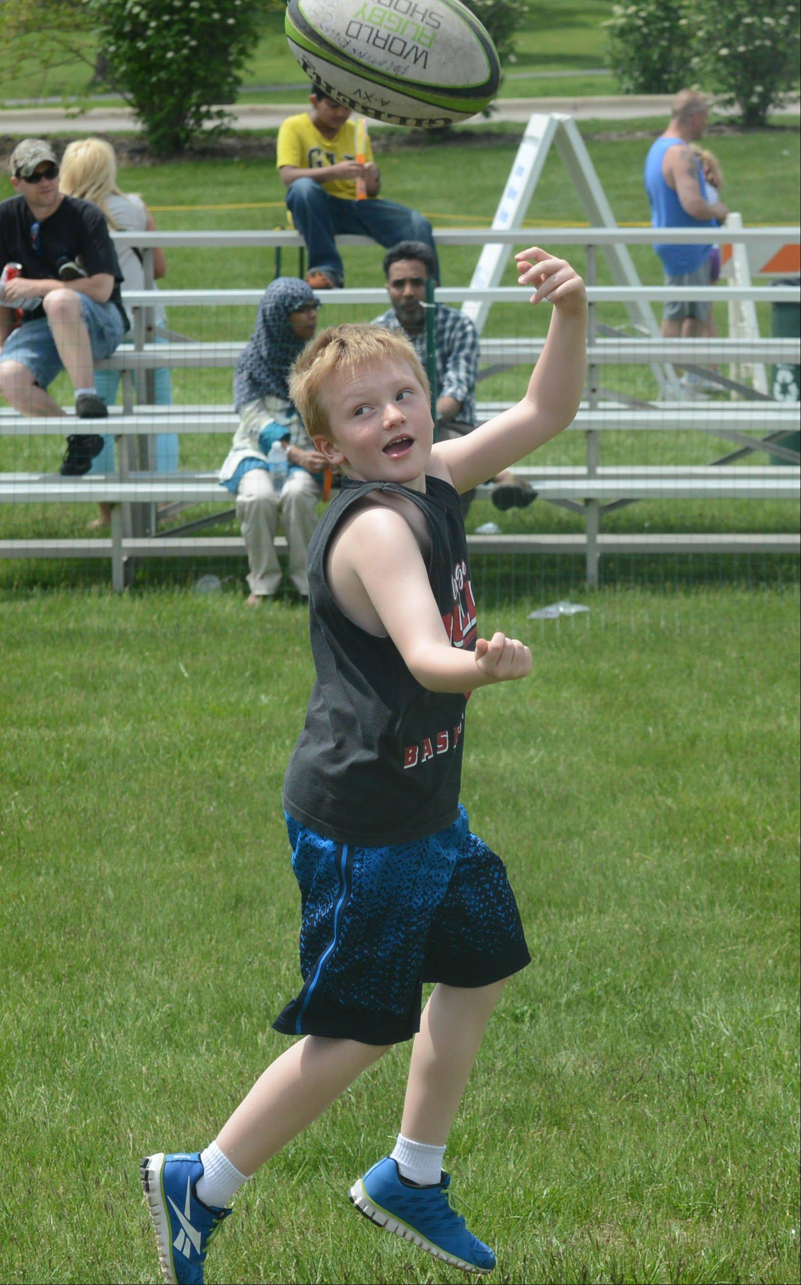 Matthew Kaczor, 7, of Palatine tosses a rugby ball during the eighth annual JustPlay! Sports & Rec Festival in Carol Stream Saturday.