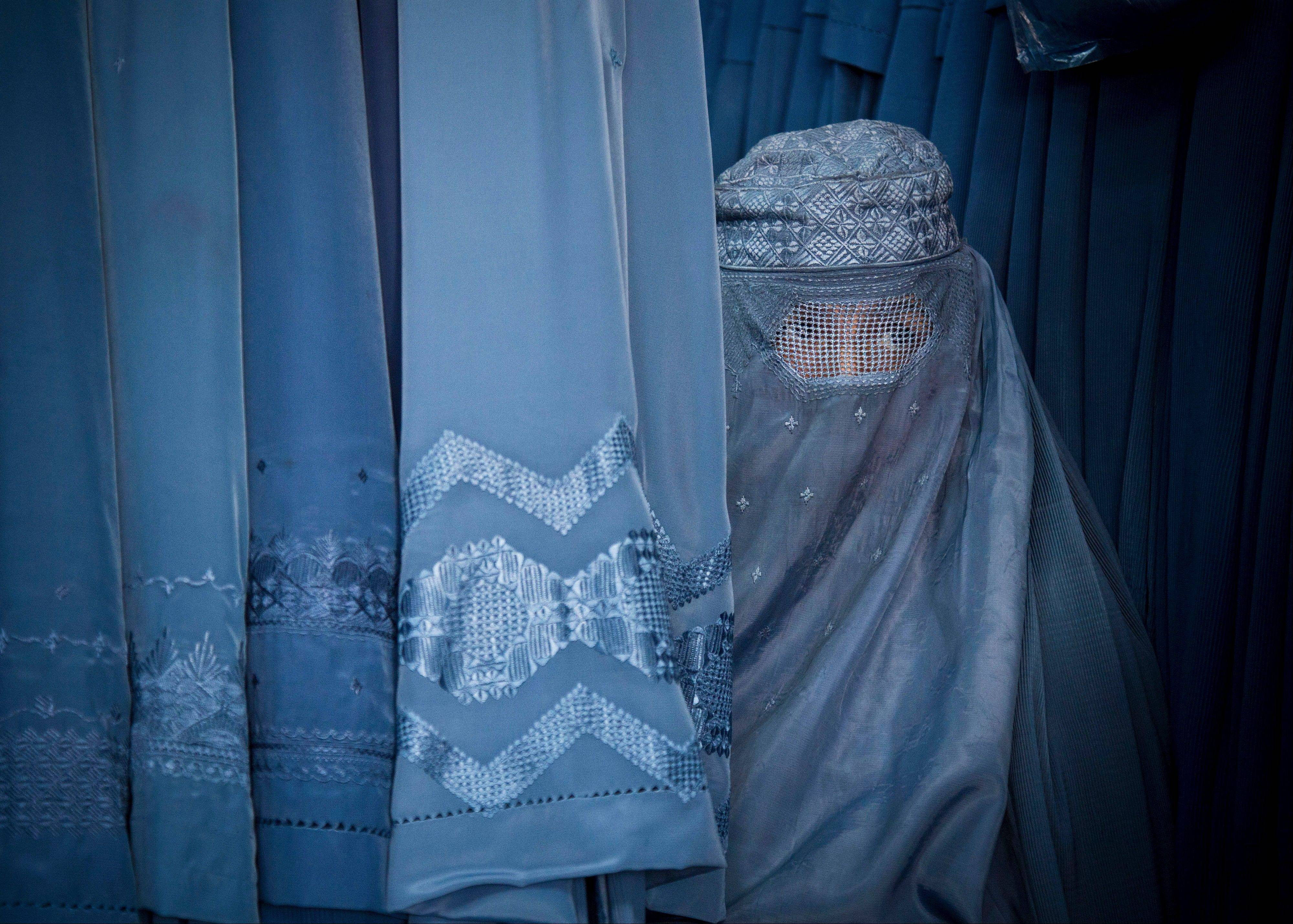 An Afghan woman peers through the eye slit of her burqa as she waits to try on a new burqa in shop in the old town of Kabul, Afghanistan. Conservative religious lawmakers in Afghanistan blocked a law on Saturday that aims to protect women's freedoms, with some arguing that parts of it violate Islamic principles or encourage women to have sex outside of marriage.