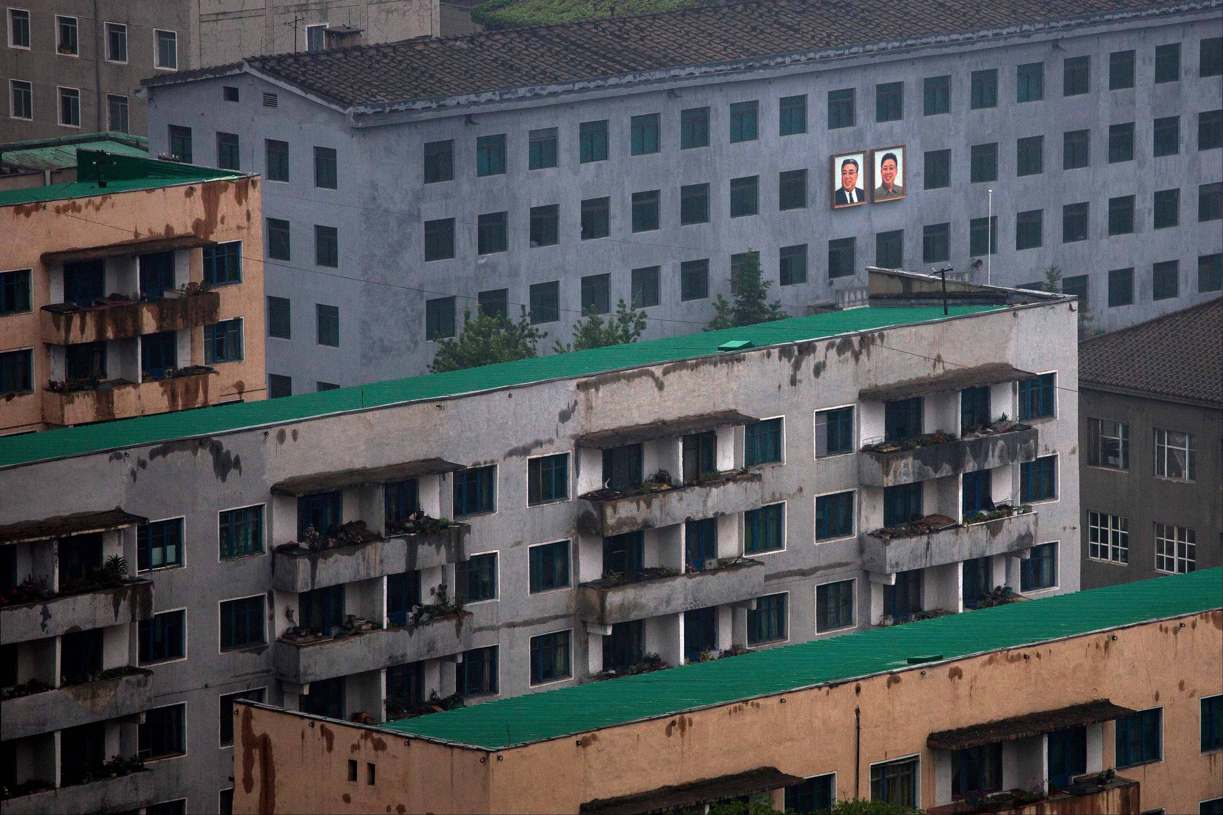 Portraits of the late North Korean leaders Kim Il Sung, left, and Kim Jong Il hang Saturday on the outside of a building in central Pyongyang, North Korea.