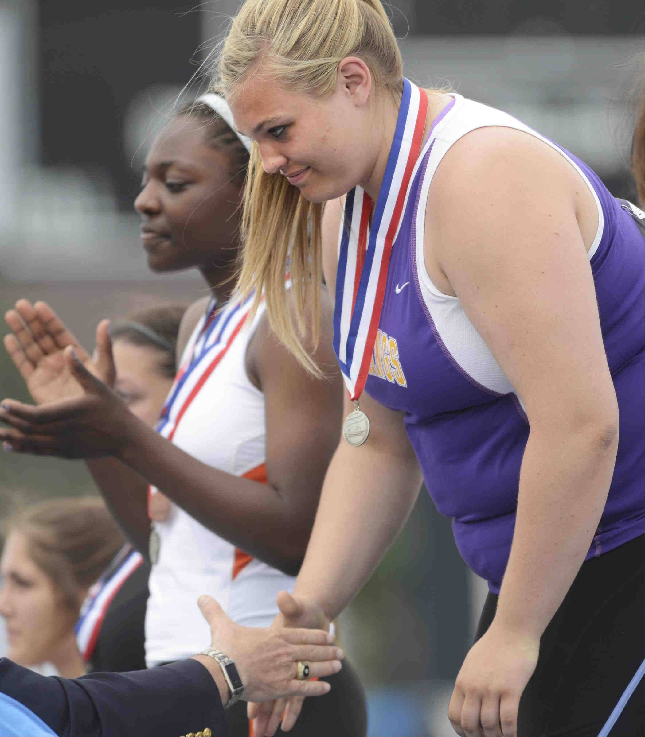 Rolling Meadows's Morgan Keller accepts her second place medal in the shot put Saturday at the Class 3A girls state track and field finals at O'Brien Stadium at Eastern Illinois University in Charleston.