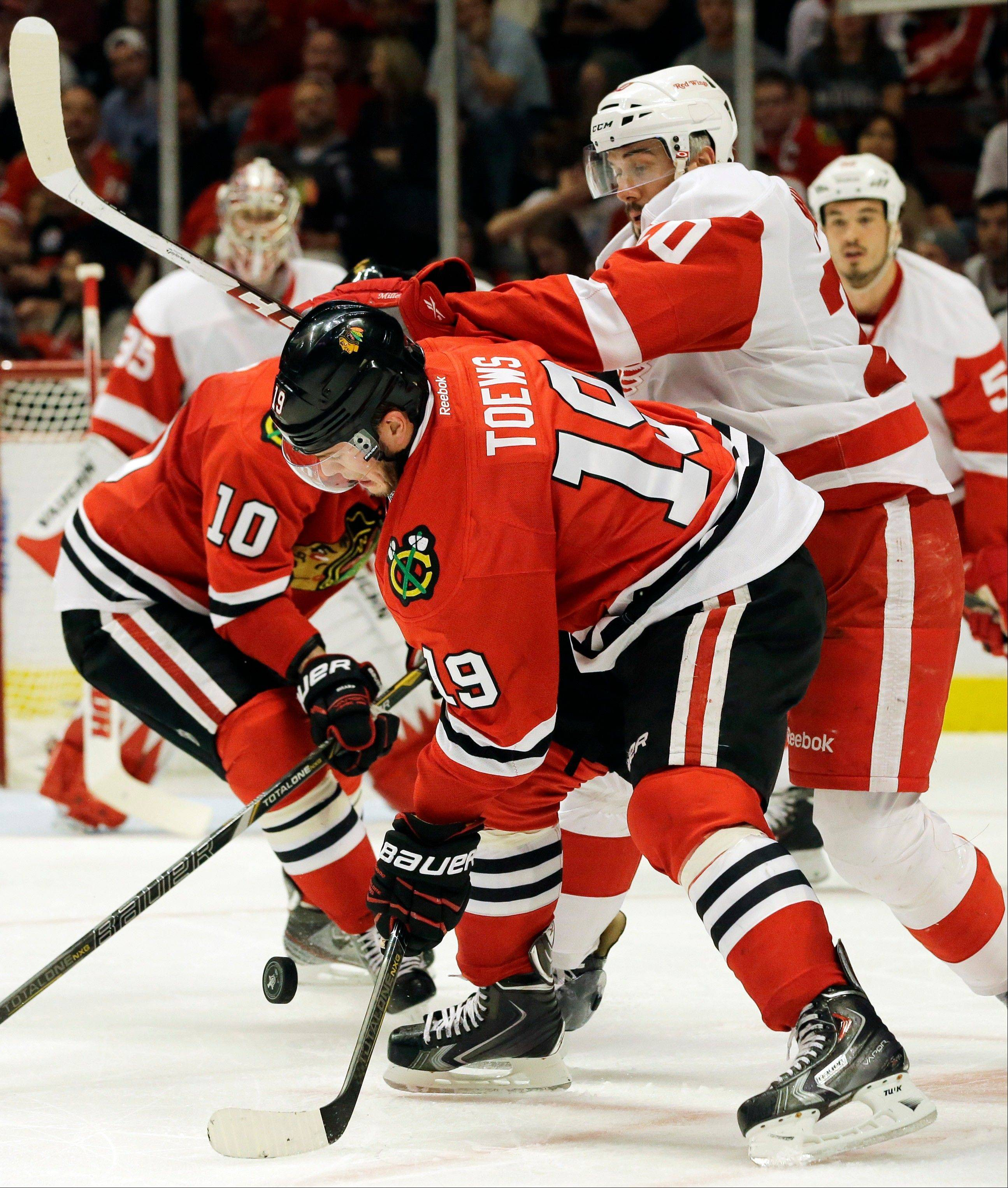 Jonathan Toews controls the puck against Detroit Red Wings' Cory Emmerton during the second period of Game 2.