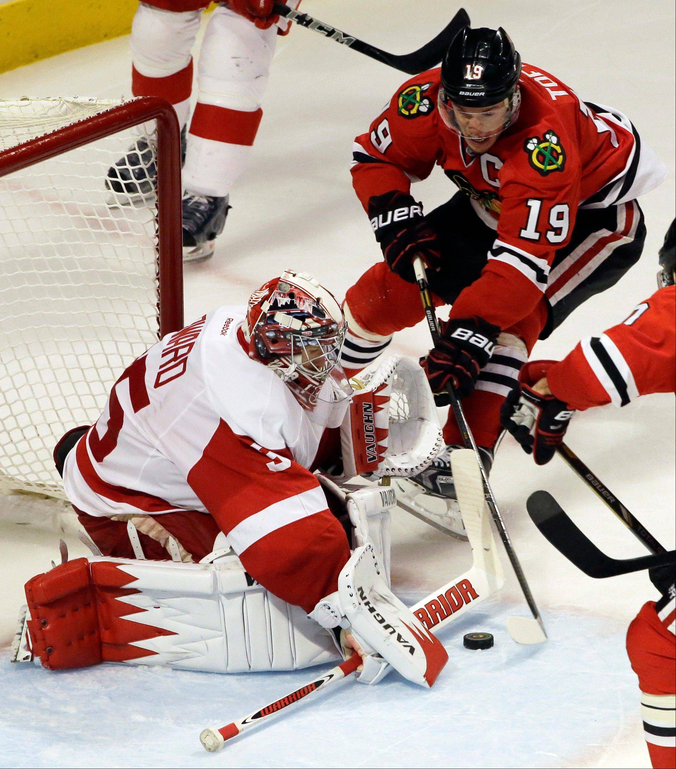 Detroit Red Wings goalie Jimmy Howard, left, saves a shot by Jonathan Toews (19) during the third period.