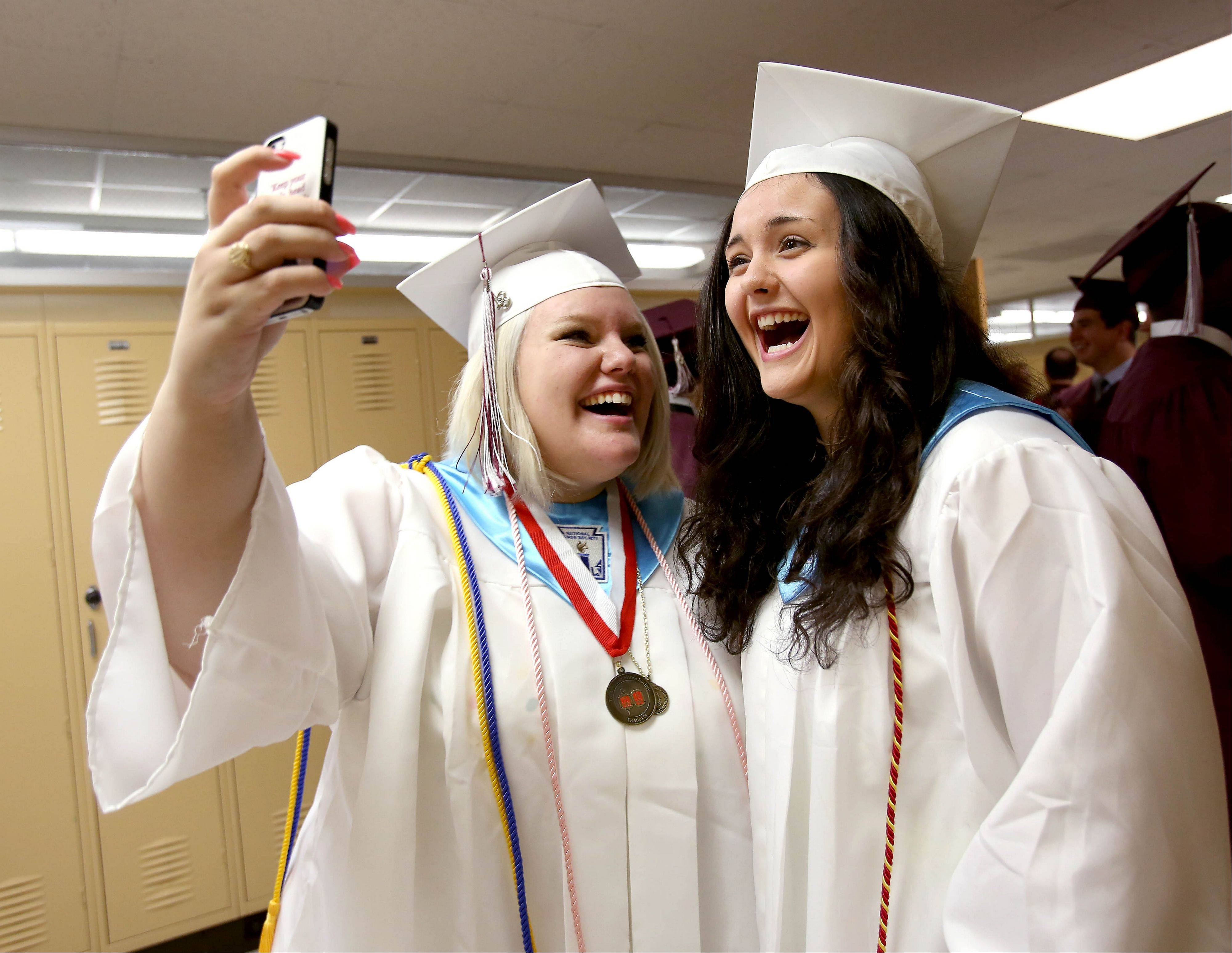 Emily Boldt, left and Kyle Hodyl, right, gets an iPhone photo before the Montini Catholic High School graduation ceremony on Sunday in Lombard. To see more photos and order reprints, visit www.dailyherald.com/galleries/news/graduations/