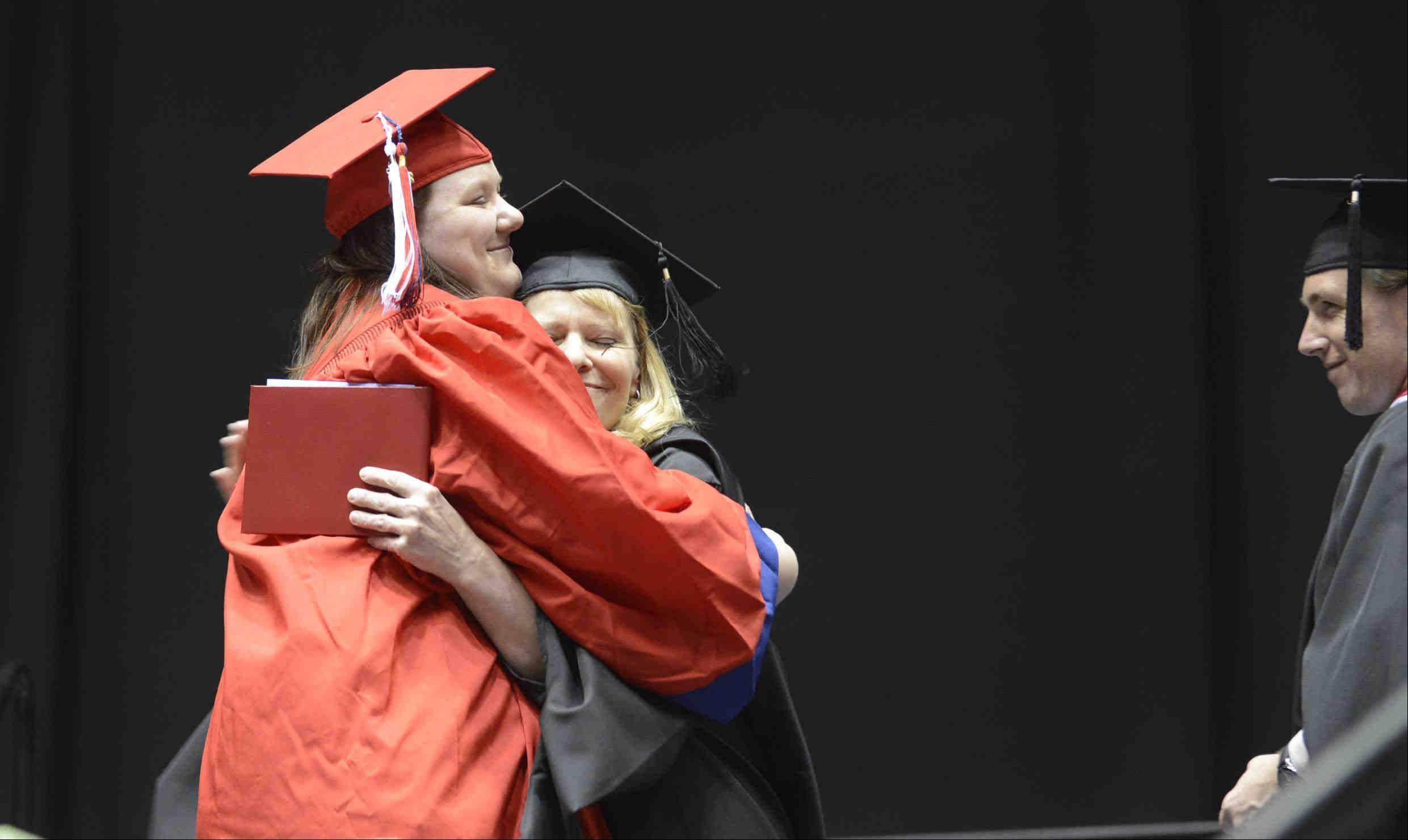 Graduate Sheah Lin Thompson hugs her mother, District 129 Board of Education member Mrs. Amie Thompson, who presented her diploma onstage Sunday during the West Aurora High School Class of 2013 commencement at Northern Illinois University in Dekalb.