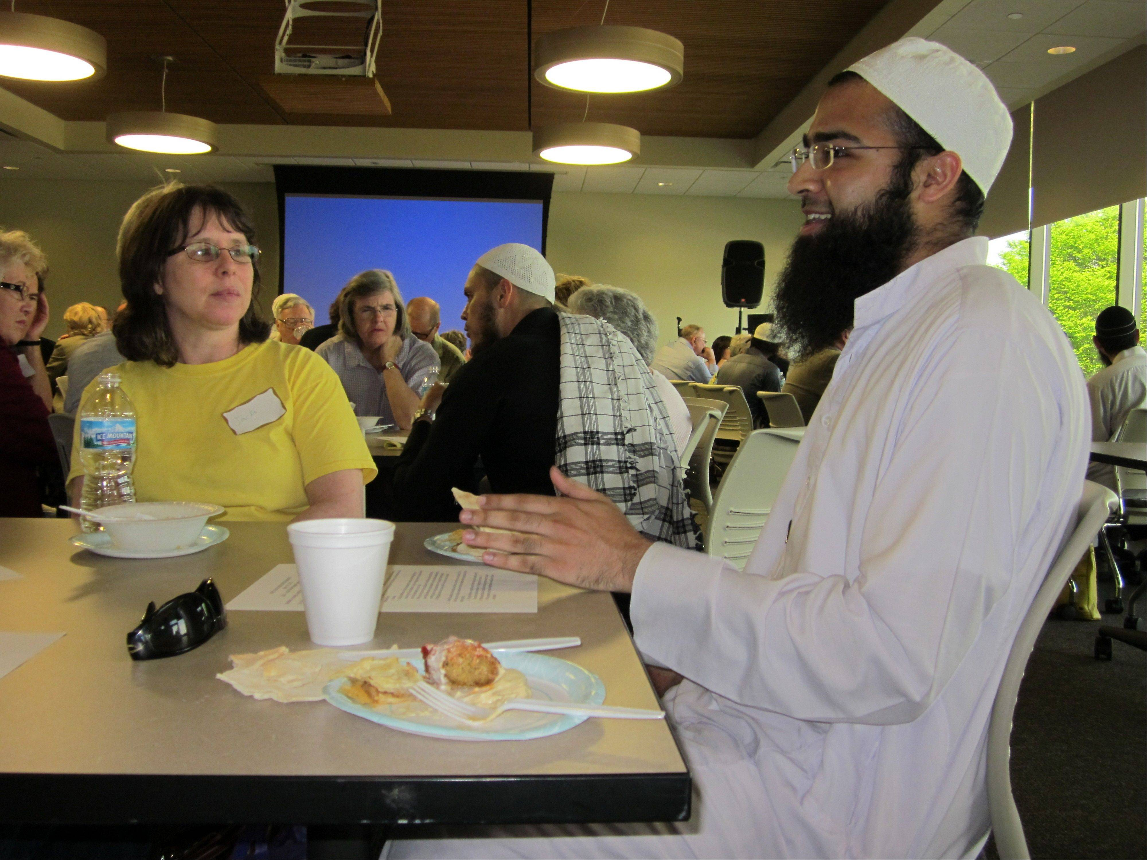 Ahsan Syed, of Bartlett, speaks during a small group session at Sunday�s �Who Is My Muslim Neighbor?� event as Jacki Bakker, of Carpentersville, listens. Syed is a student of Islam at the Institute of Islamic Education in Elgin.