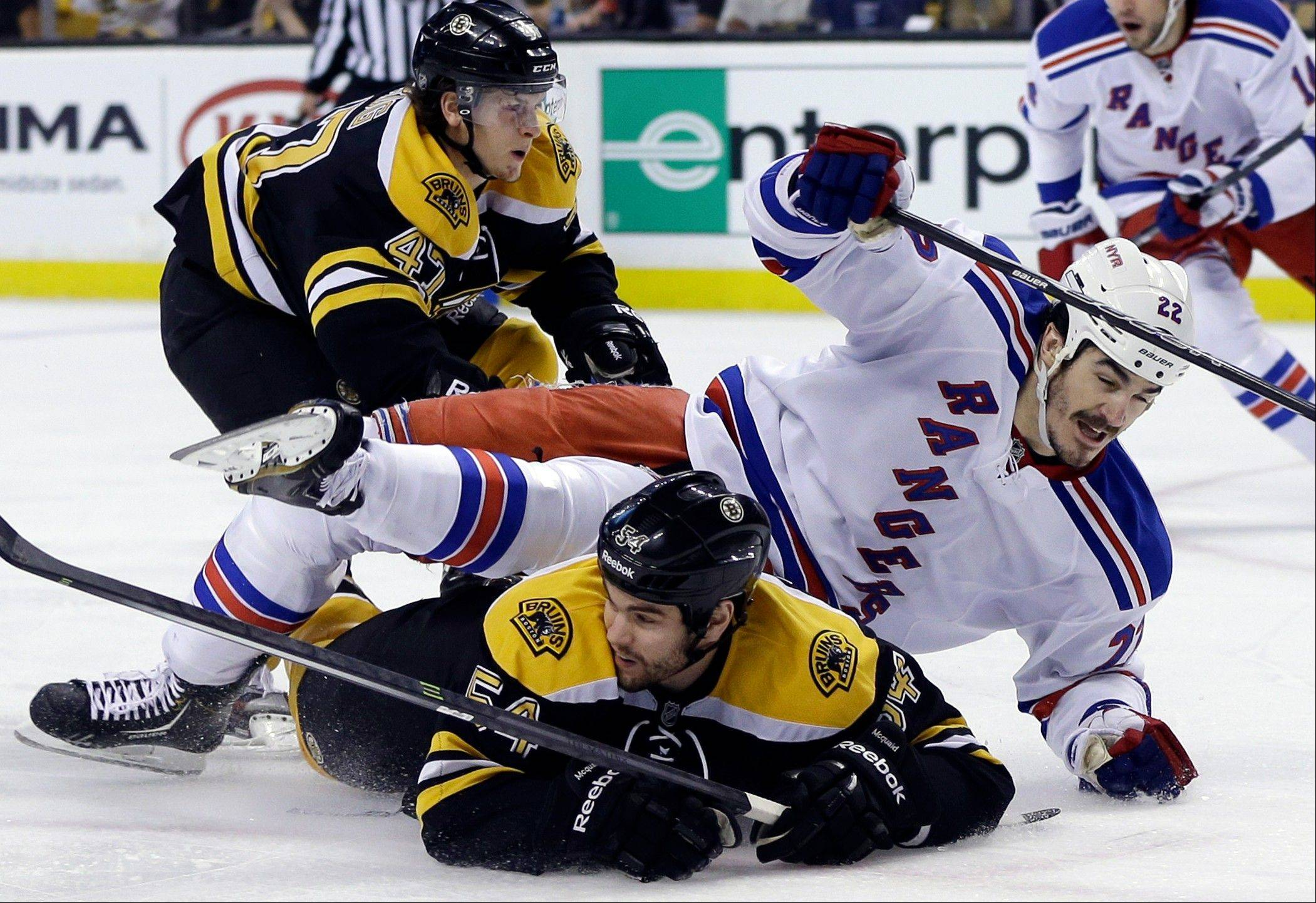 New York Rangers center Brian Boyle (22) goes down to the ice as he chases the puck against Boston Bruins defensemen Adam McQuaid (54) and Torey Krug (47) during the first period in Game 2 of the NHL Eastern Conference semifinal hockey playoff series in Boston, Sunday, May 19, 2013.
