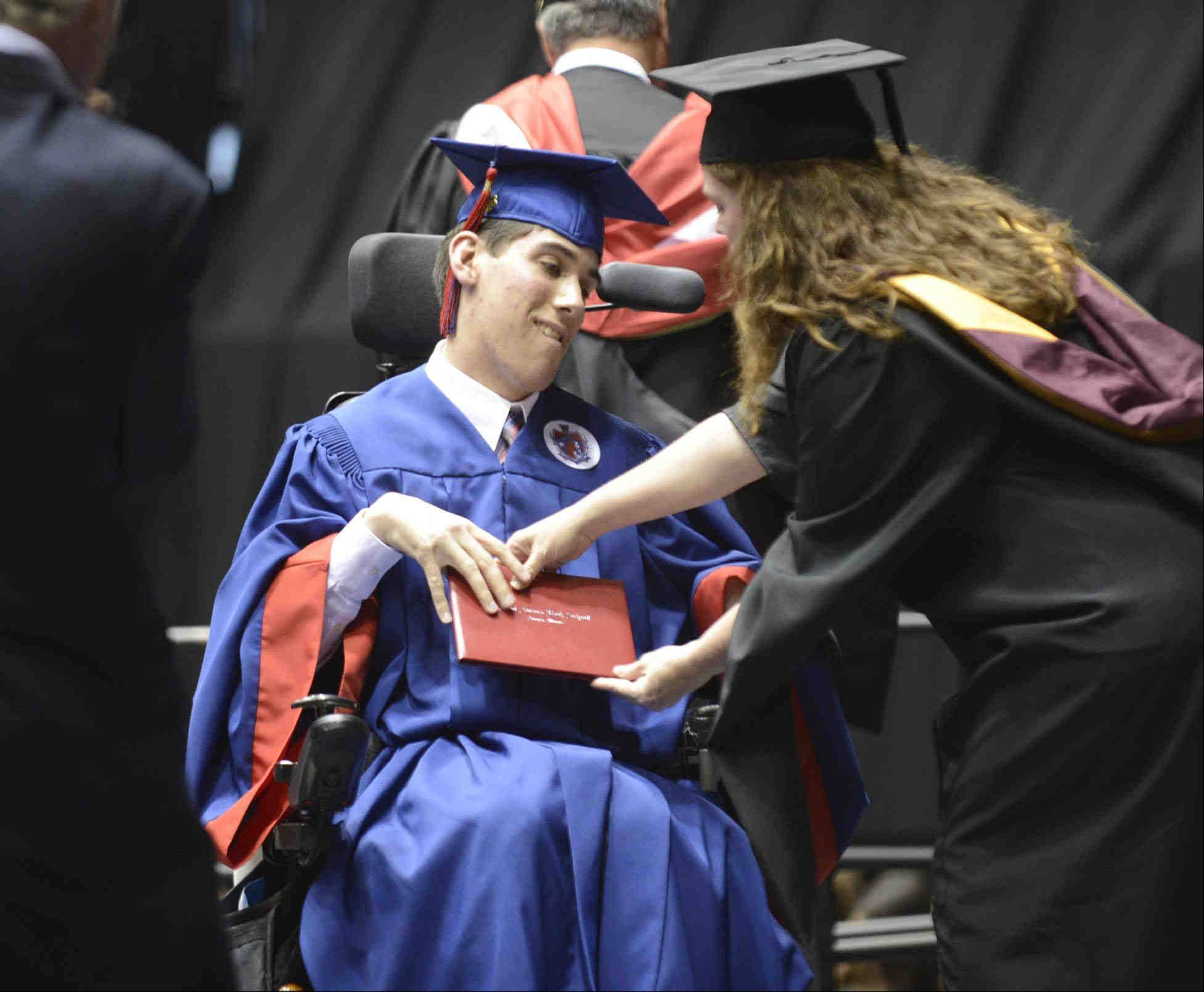 Graduate Todd James Nordone accepts his diploma Sunday during the West Aurora High School Class of 2013 commencement at Northern Illinois University in Dekalb.