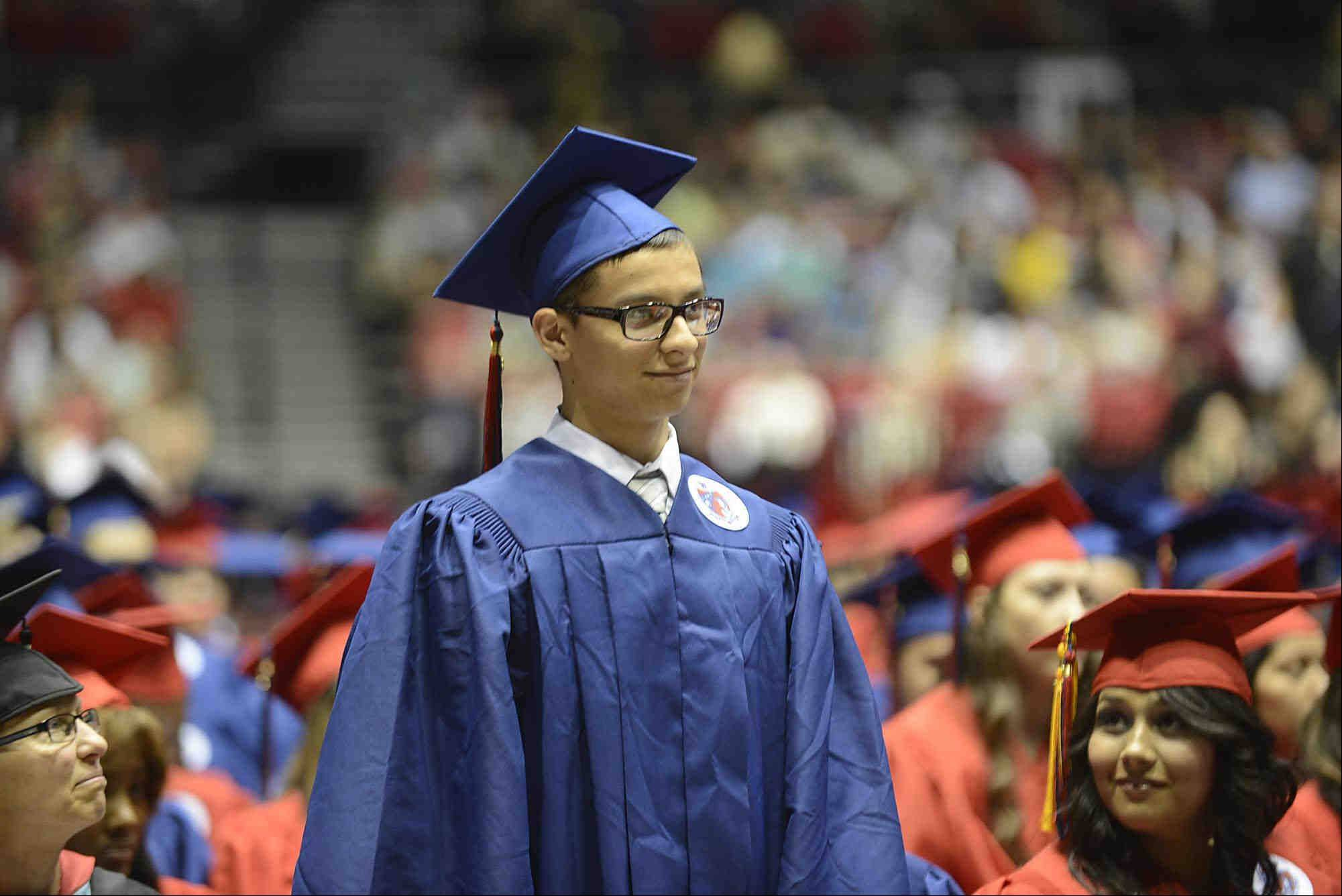 Graduate Robert Isaiah Acosta stands as he is introduced during the West Aurora High School Class of 2013 commencement at Northern Illinois University in Dekalb. He is joining the US armed forces.