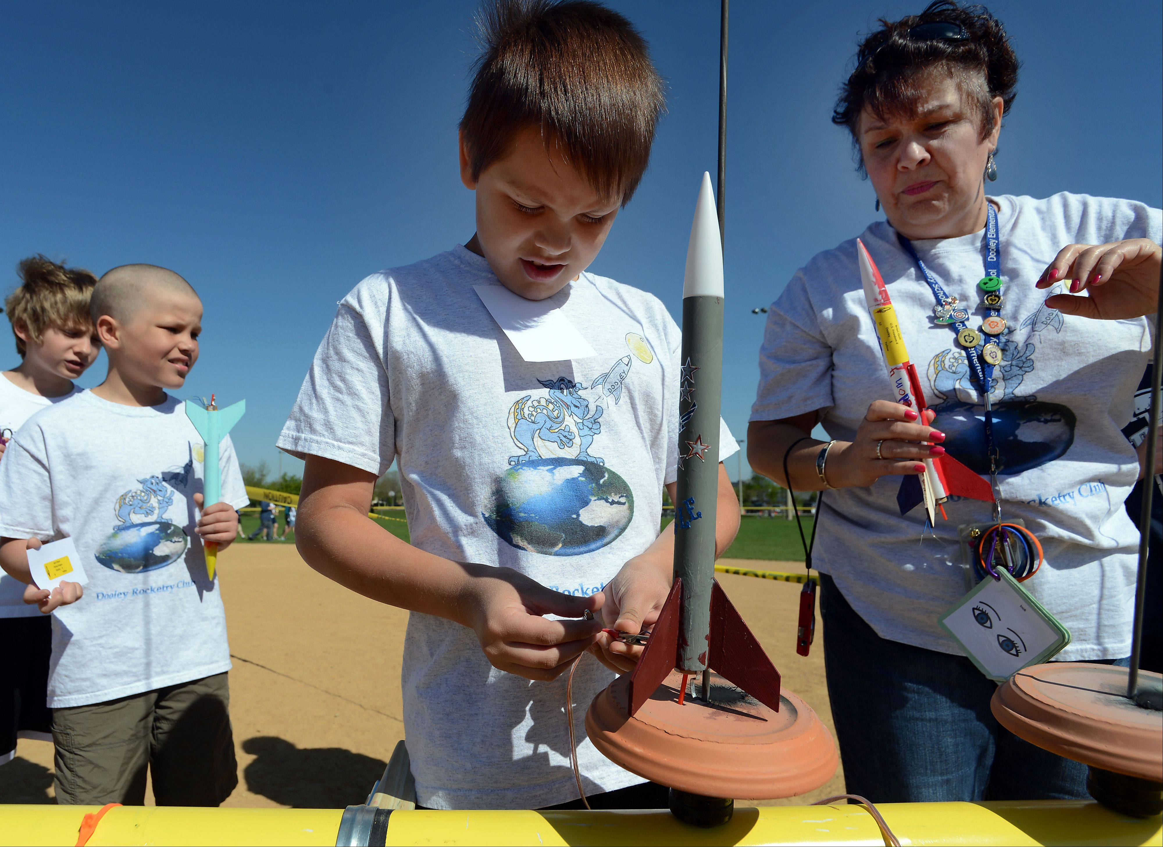 Donald McCormick, 10, in the 4th grade at Thomas Dooley Elementary School in Schaumburg, hooks up his rocket, called the Red Eagle, at Olympic Park in Schaumburg. His was just one of 450 rockets that took to the sky as part of school district 54 rocket launch day. Next to him is Joann Delmedico who was the rocketeer club facilitator on site.