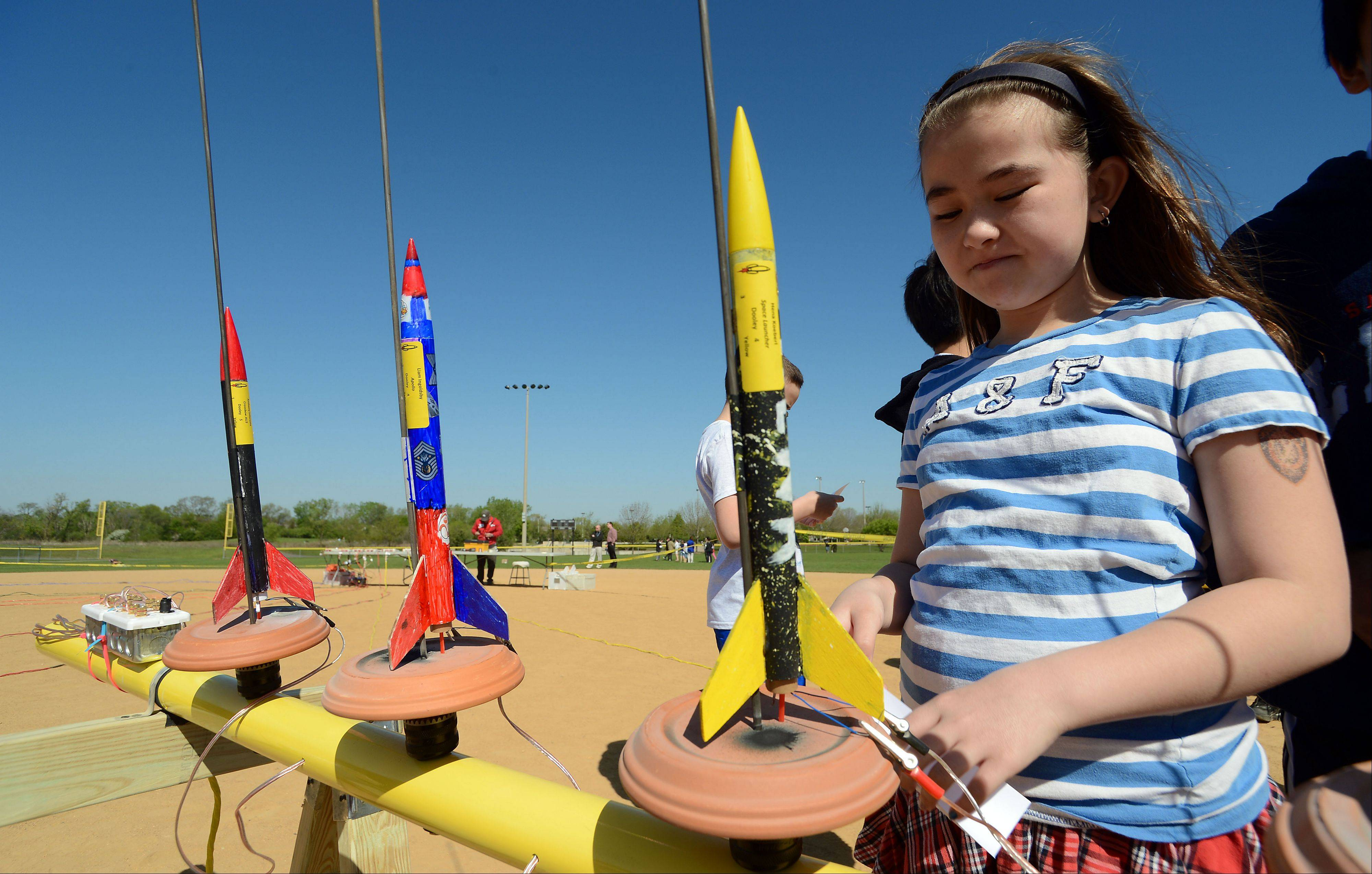 Thomas Dooley Elementary School fourth grader Hena Koeberl hooks up her rocket, called the Space Launcher, at Olympic Park in Schaumburg. Her rocket was just one of 450 rockets that took to the sky as part of school district 54 rocket launch day.