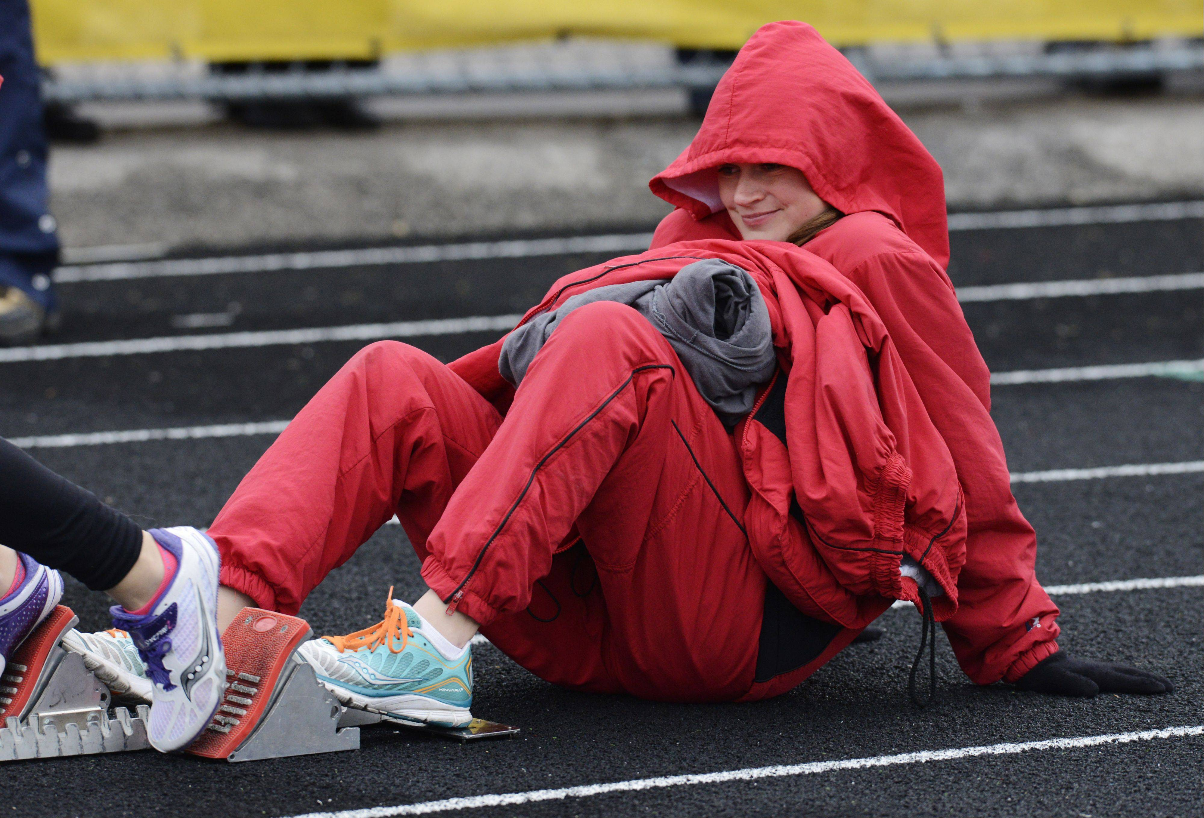 On an unseasonably cool May evening, Barrington's Ingrid Peterson is bundled against the elements as she holds the starting block for a Fillies runner in the 400 meter relay during the Mid-Suburban League girls track meet at Schaumburg High School.