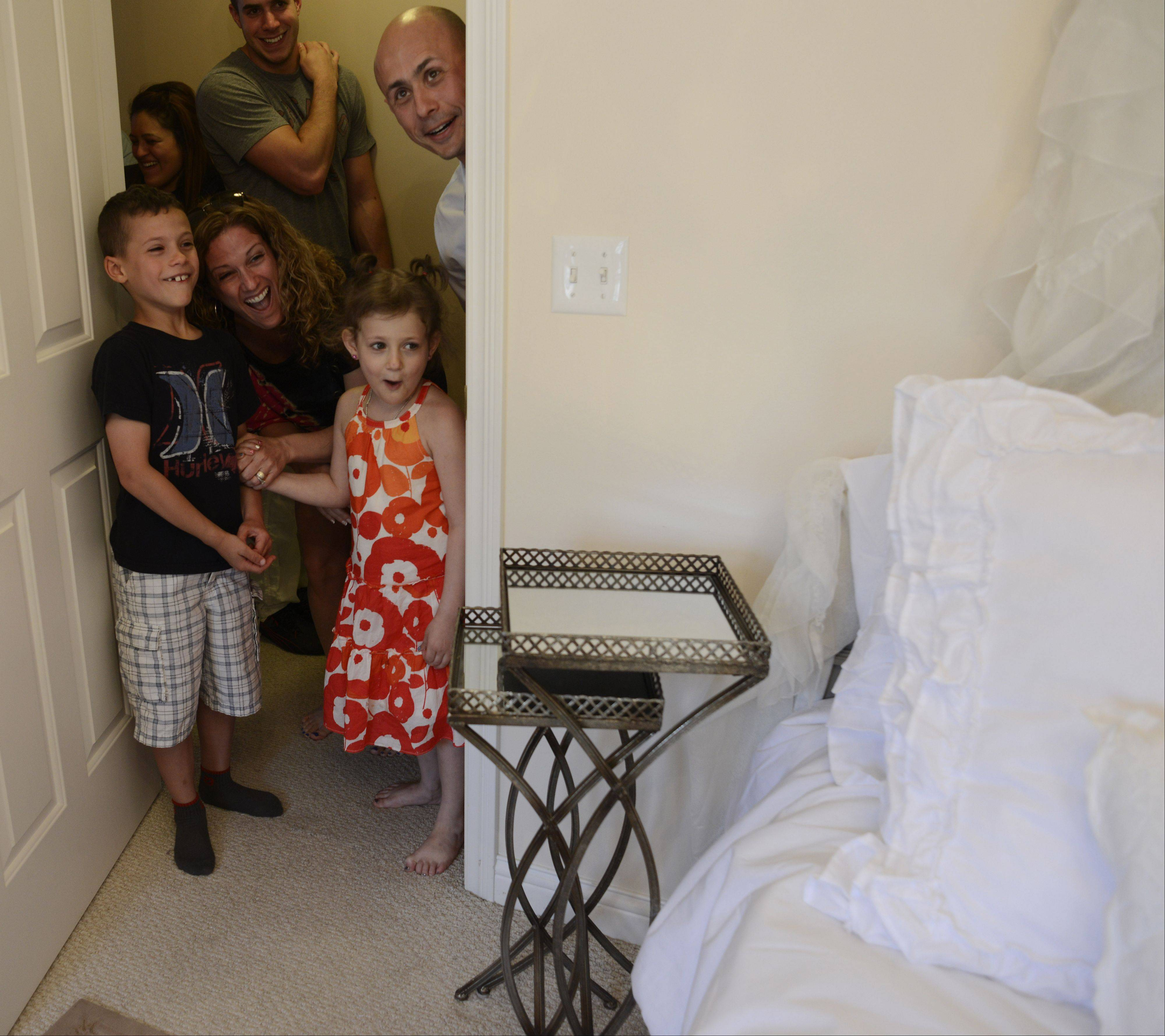Kennedy Khalimsky, 6, of Palatine, reacts to her bedroom-makeover provided by the new Chicago-area chapter of Special Spaces National. Kennedy has been diagnosed with leukemia and is undergoing treatment. With her are her brother, Maddox, 8, her mom, Edan Gelt, and her dad, Gene Khalimsky, right.