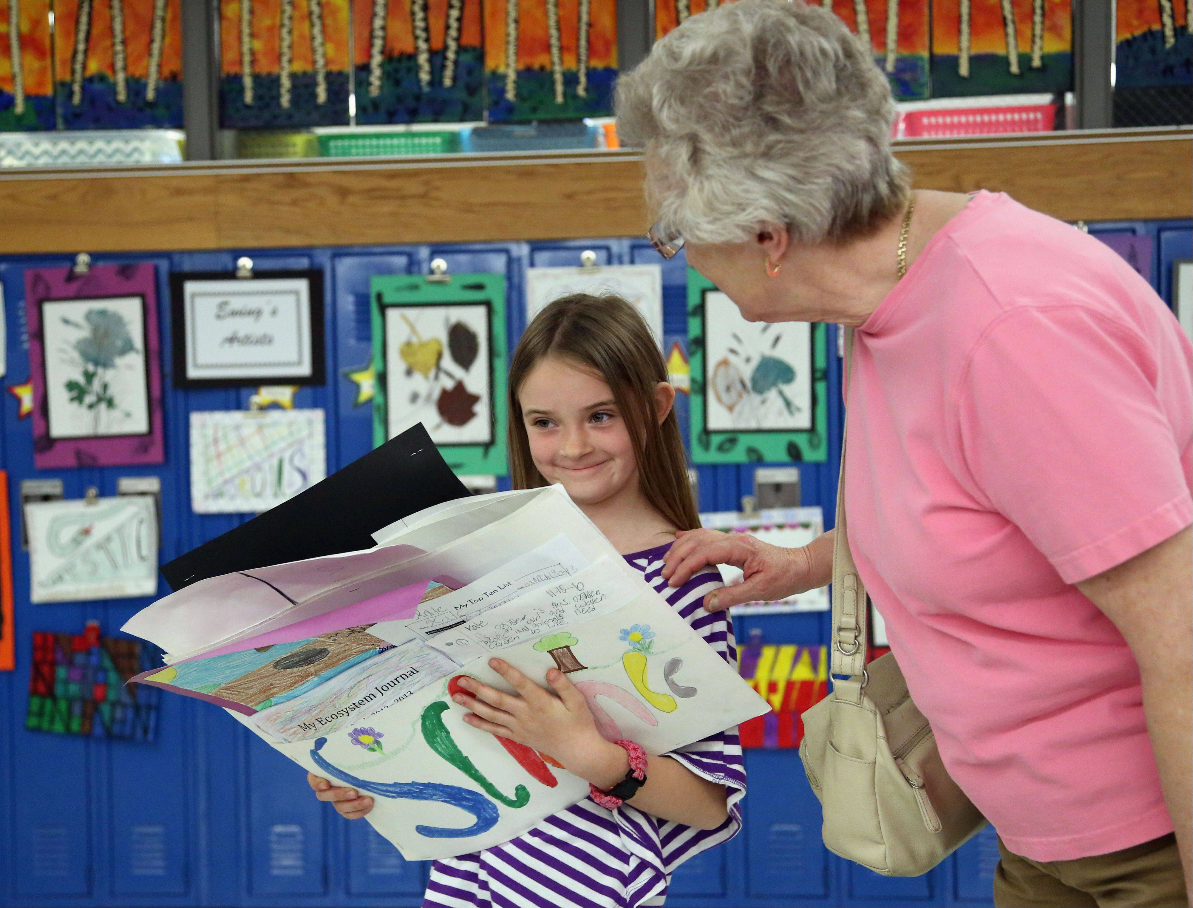 Third grader Kate Driscoll, left, carries her art projects with her grandmother Bjorg Davis, of Mundelein, during an event called Learning and the Arts at Mechanics Grove School Wednesday.