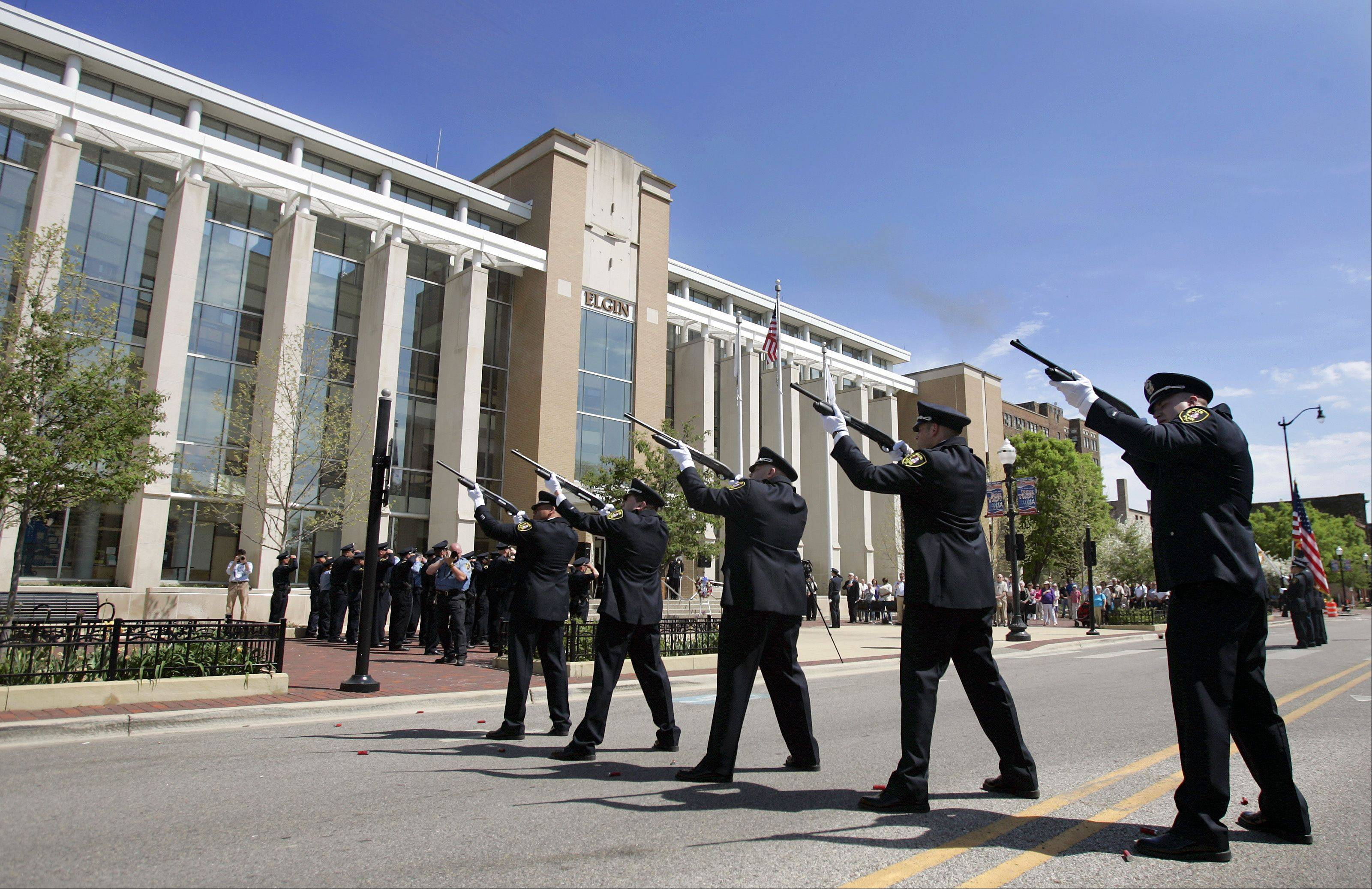 The firing detail fires off three volleys as taps is played from the parking deck during the 2013 Elgin Police Department Memorial Service Wednesday.