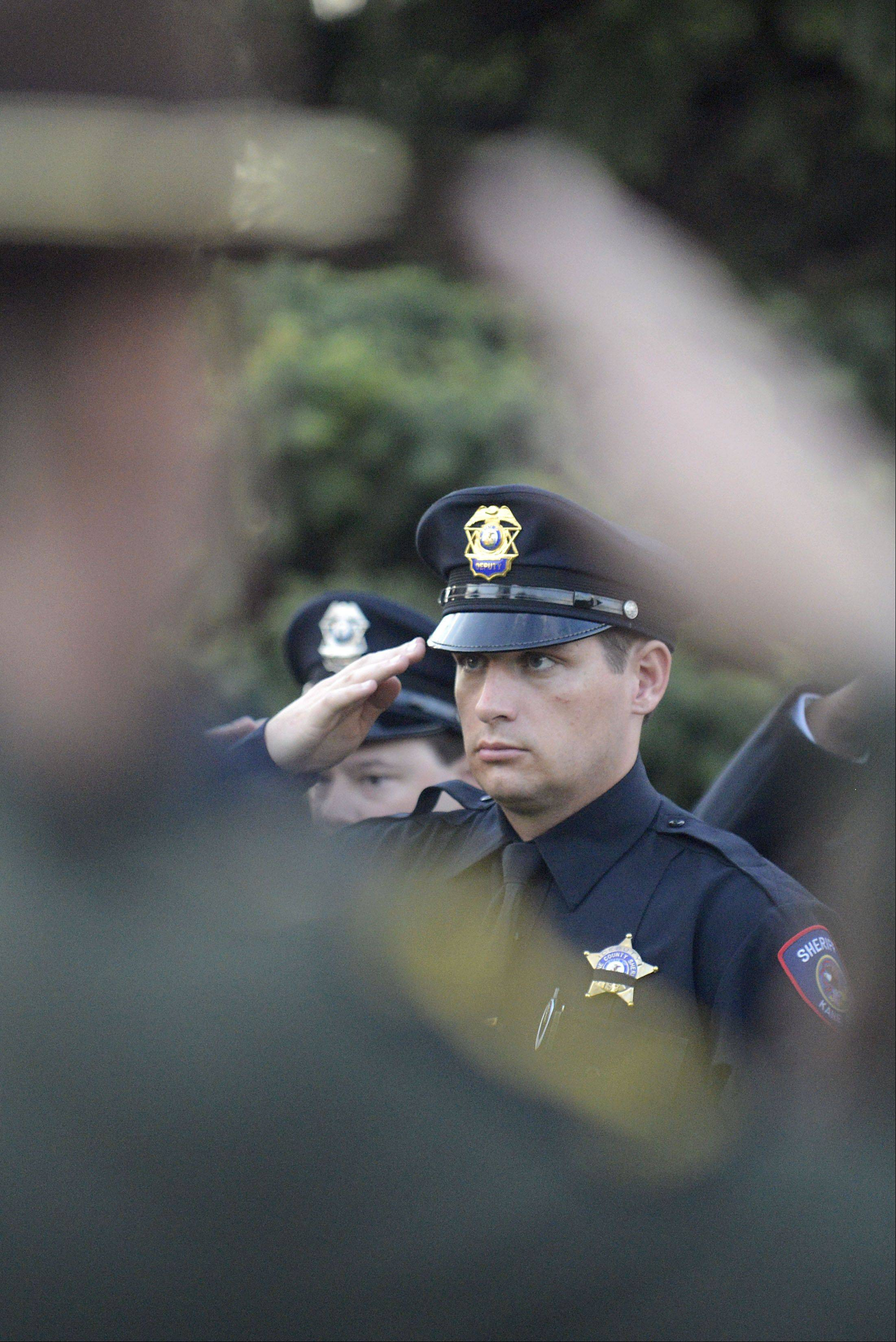 Framed by a saluting Illinois State Trooper's hand, Kane County Sheriff Deputy Ryan Monaghan salutes while taps is played at the Kane County Chiefs of Police Association's annual Law Enforcement Appreciation Ceremony at Mooseheart House of God church in Batavia Wednesday.
