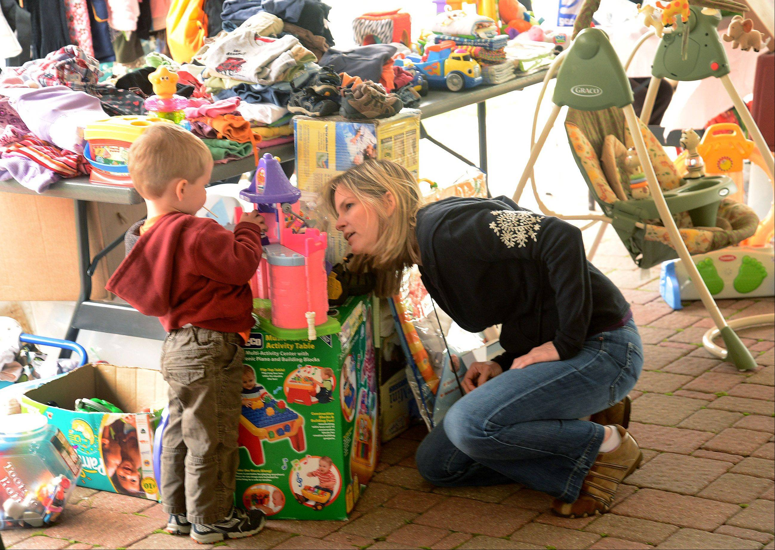 Robyn Russo of Arlington Heights and her 2-year-old son Matthew shop for childrens toys and books at the Salt Creek Rural Park District's community garage sale at Twin Lakes Recreation Area in Palatine.