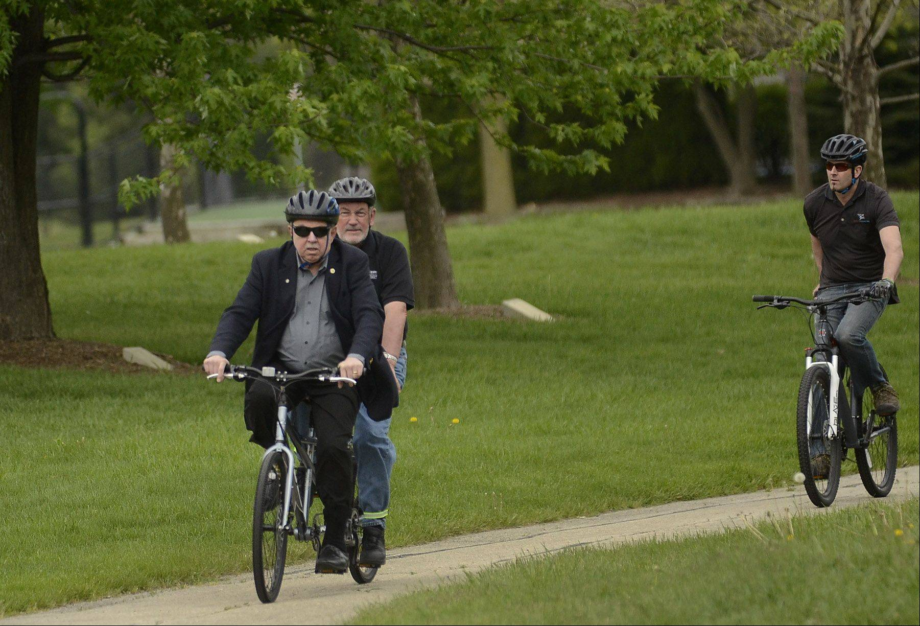 Schaumburg Mayor Al Larson and Park District Commissioner Bob Schmidt make their way to the village hall as they lead a bike ride from the Meineke Recreation Center to the village hall to commemorate Bike to Work Week.
