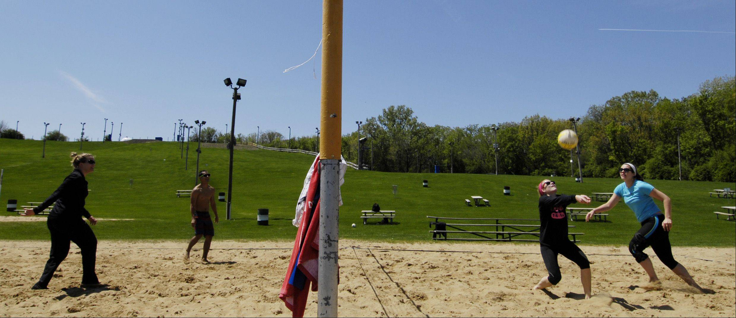 Sisters Colleen and Nora Mitros, right, play sand volleyball with some friends at Four Lakes in Lisle, Monday.