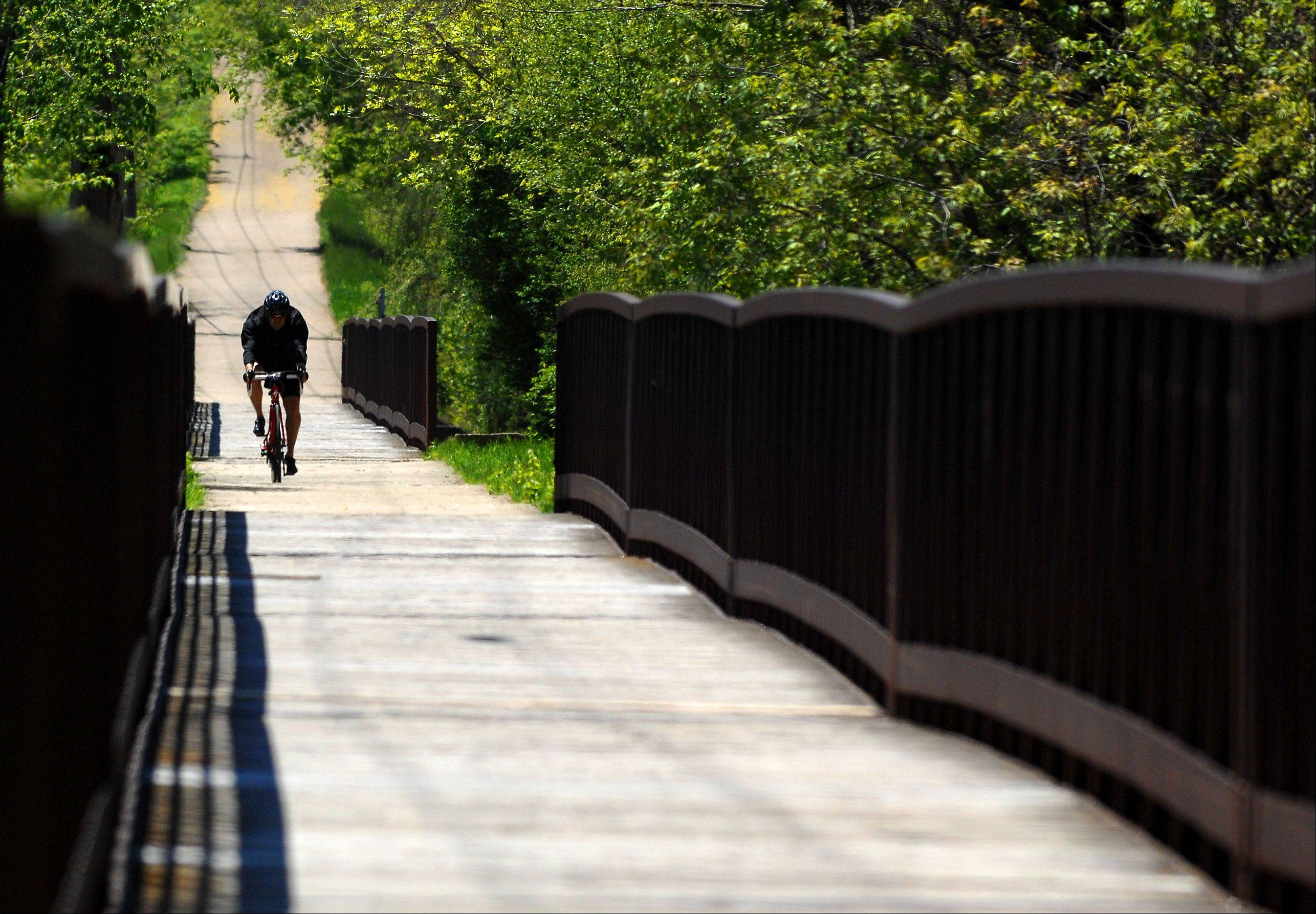 A biker approaches the bike trail bridge to cross over the Fox River and into the Jon Duerr Forest Preserve in South Elgin Monday afternoon.