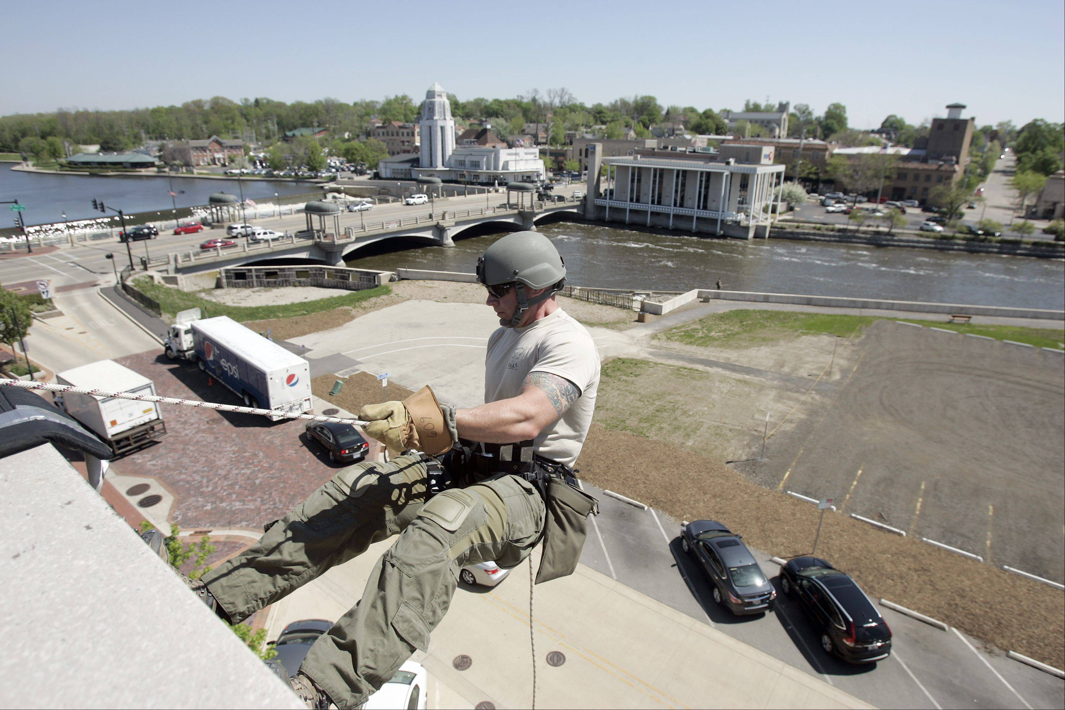 With the Fox River for a backdrop, Kane County Sheriff's Deputy and SWAT team member Chris Peeler takes a giant first step as he launches himself downward. The Kane County Swat Team was repelling from the parking garage in St. Charles Tuesday as they trained.