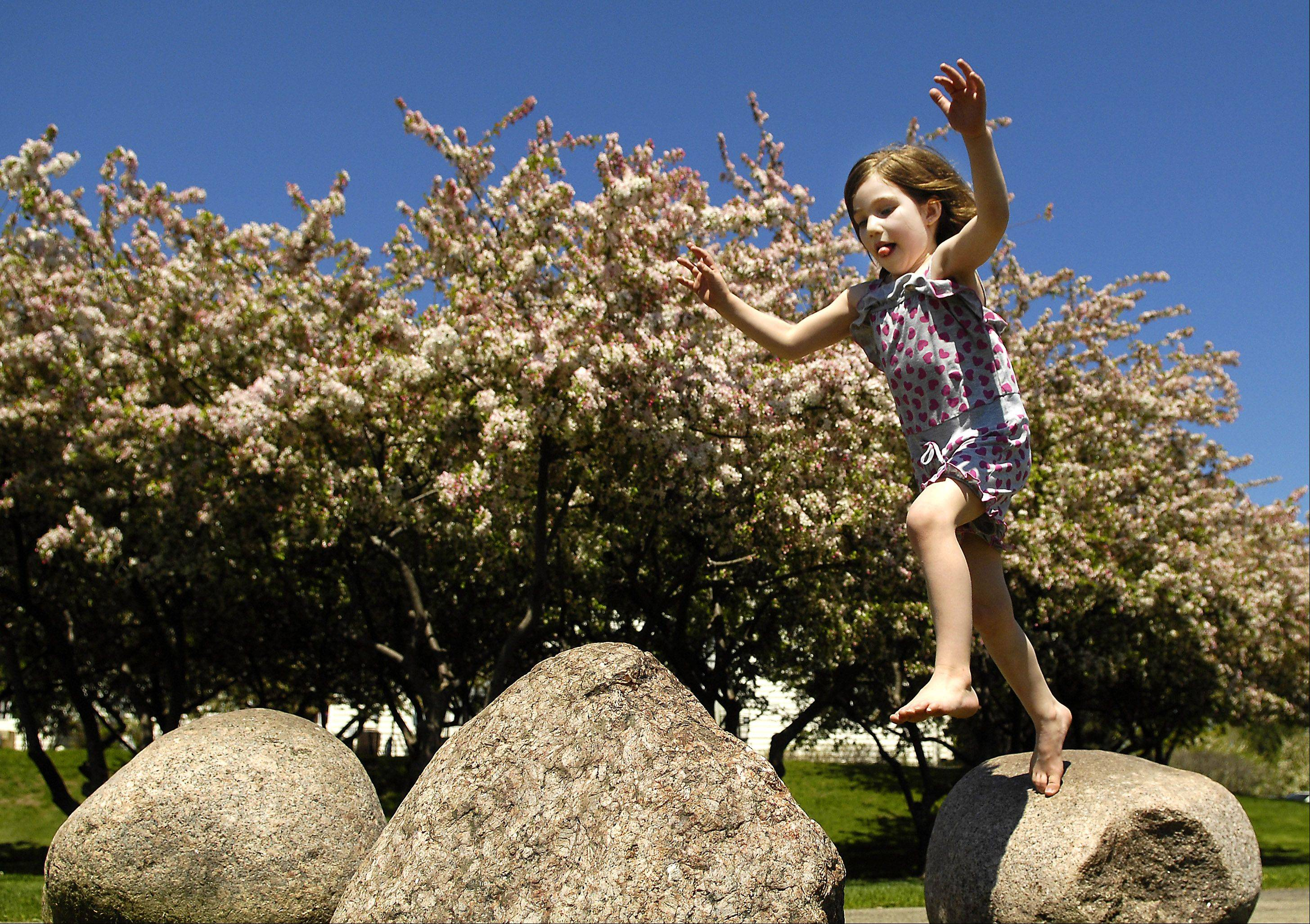 Amelia Schreier, 5, of Crystal Lake, jumps from rock to rock while playing at Ken Carpenter Park in Lake in the Hills Tuesday. She eventually had to quit when the sun made the rocks too hot for her.