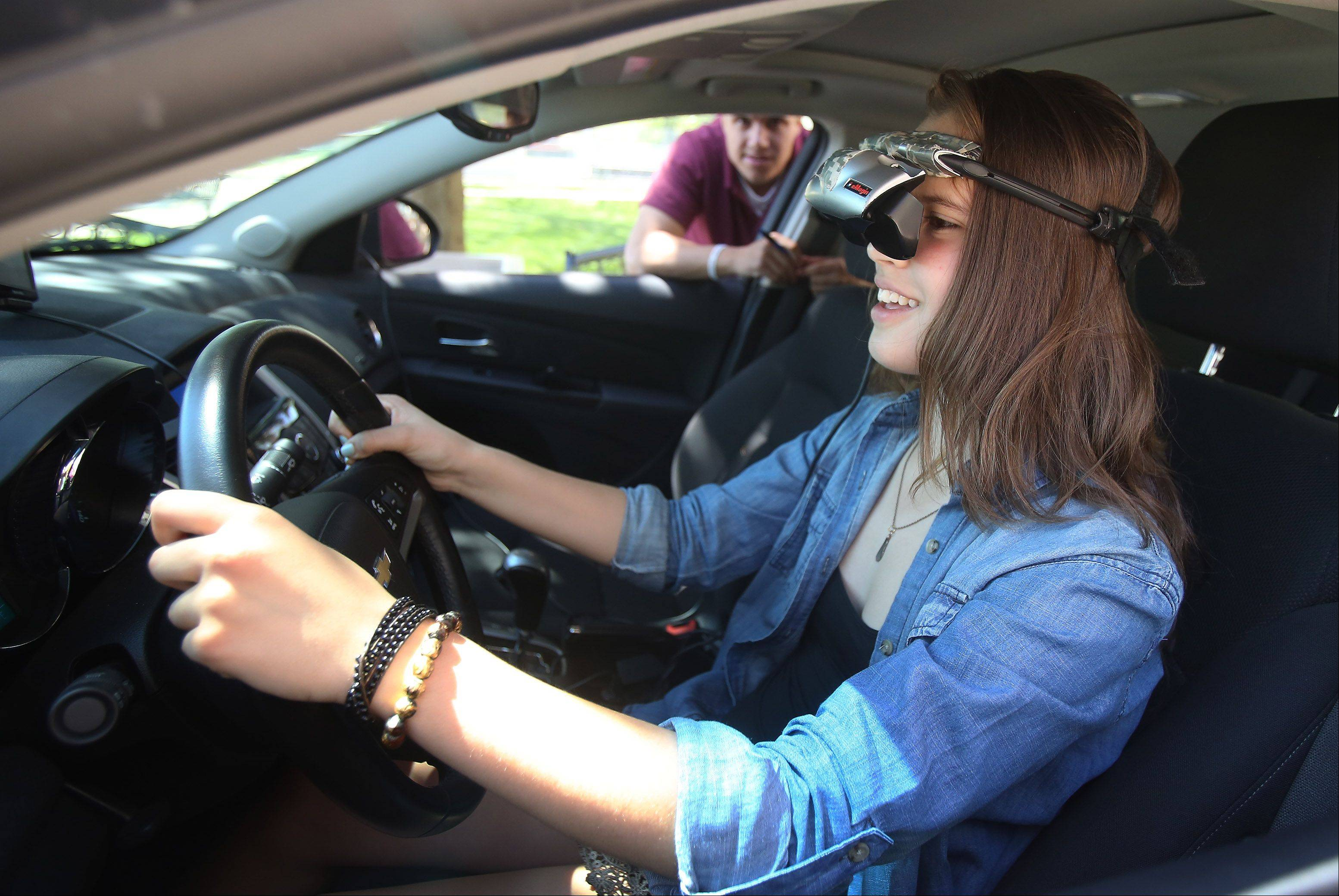 Sophomore Ava Polzin tries to drive the simulator during a distracted and drunk driving education program, in a high-tech simulator, by UNITE's ArriveAliveTour 2013 at Libertyville High School. The program helps students understand the dangers and consequences of drunk driving and texting while driving.